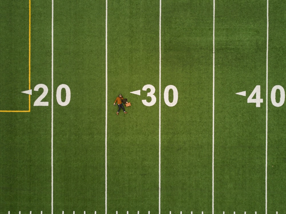 Drone aerial view of a person lying on the back on a football pitch in Montreal