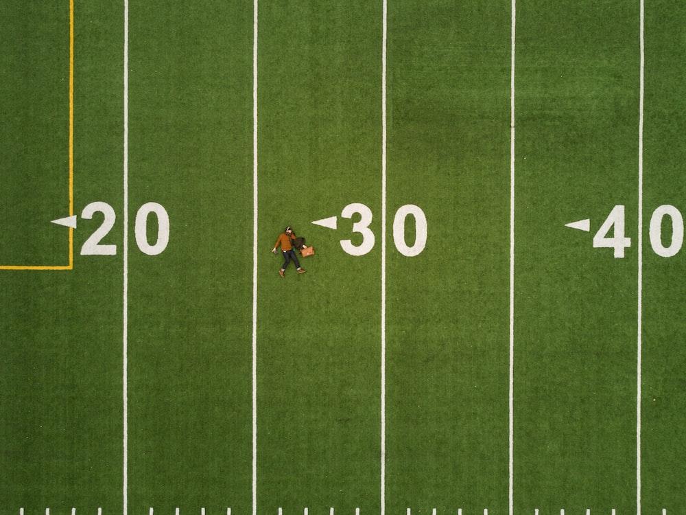 man lying on 30 yards on football field