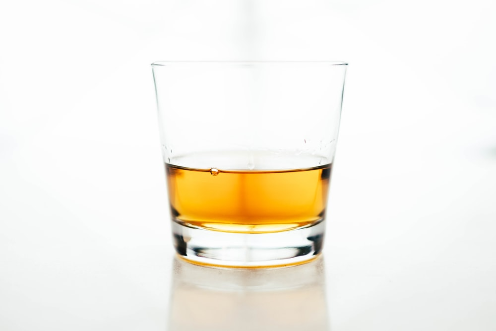 The macro view of a glass cup containing whiskey in a white background
