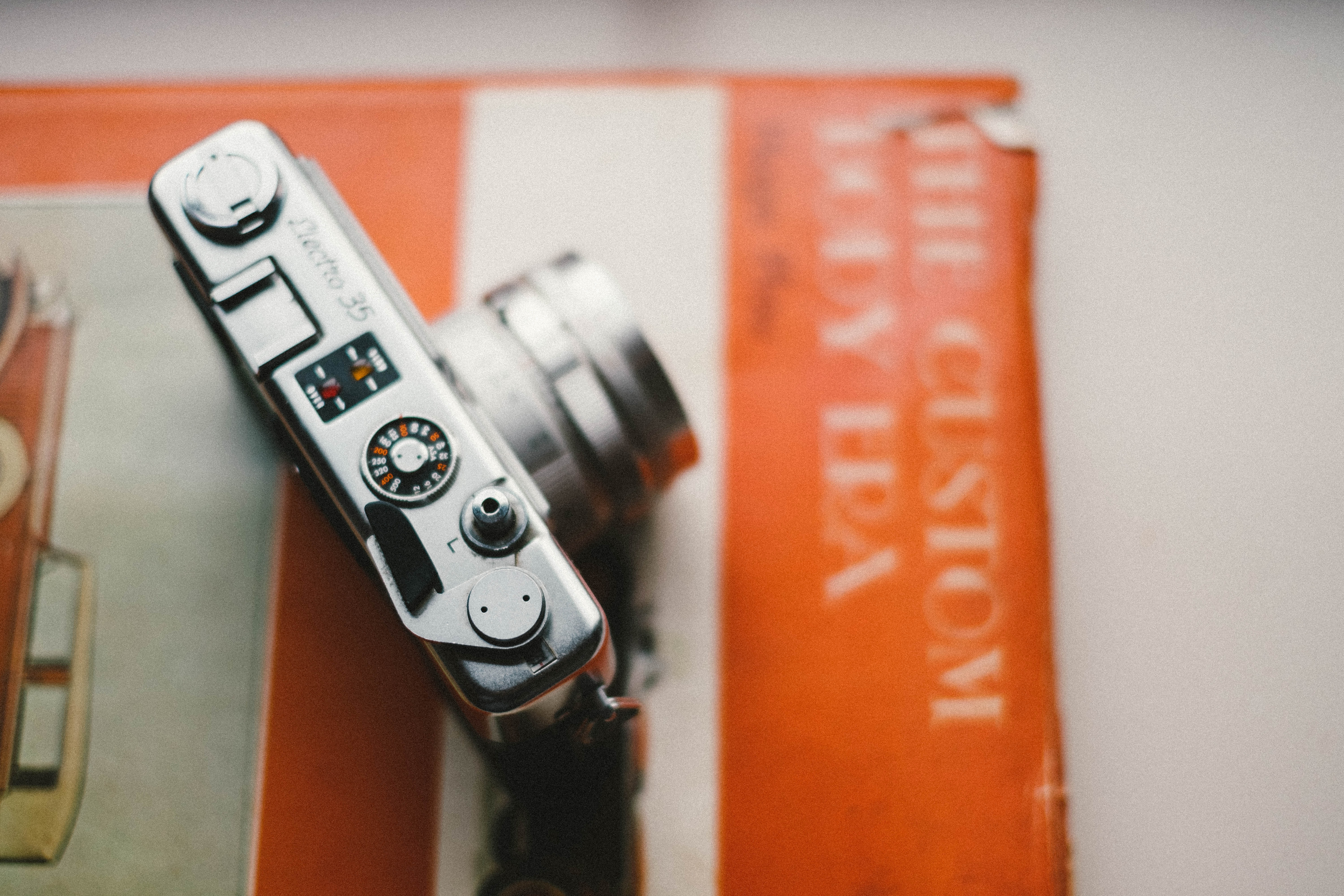 Looking down on a camera that sits atop an orange vintage book