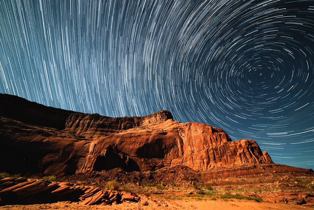 A Blurry Background Image That Perfectly Captures Swirling Stars In Night Sky Over Lake Powell