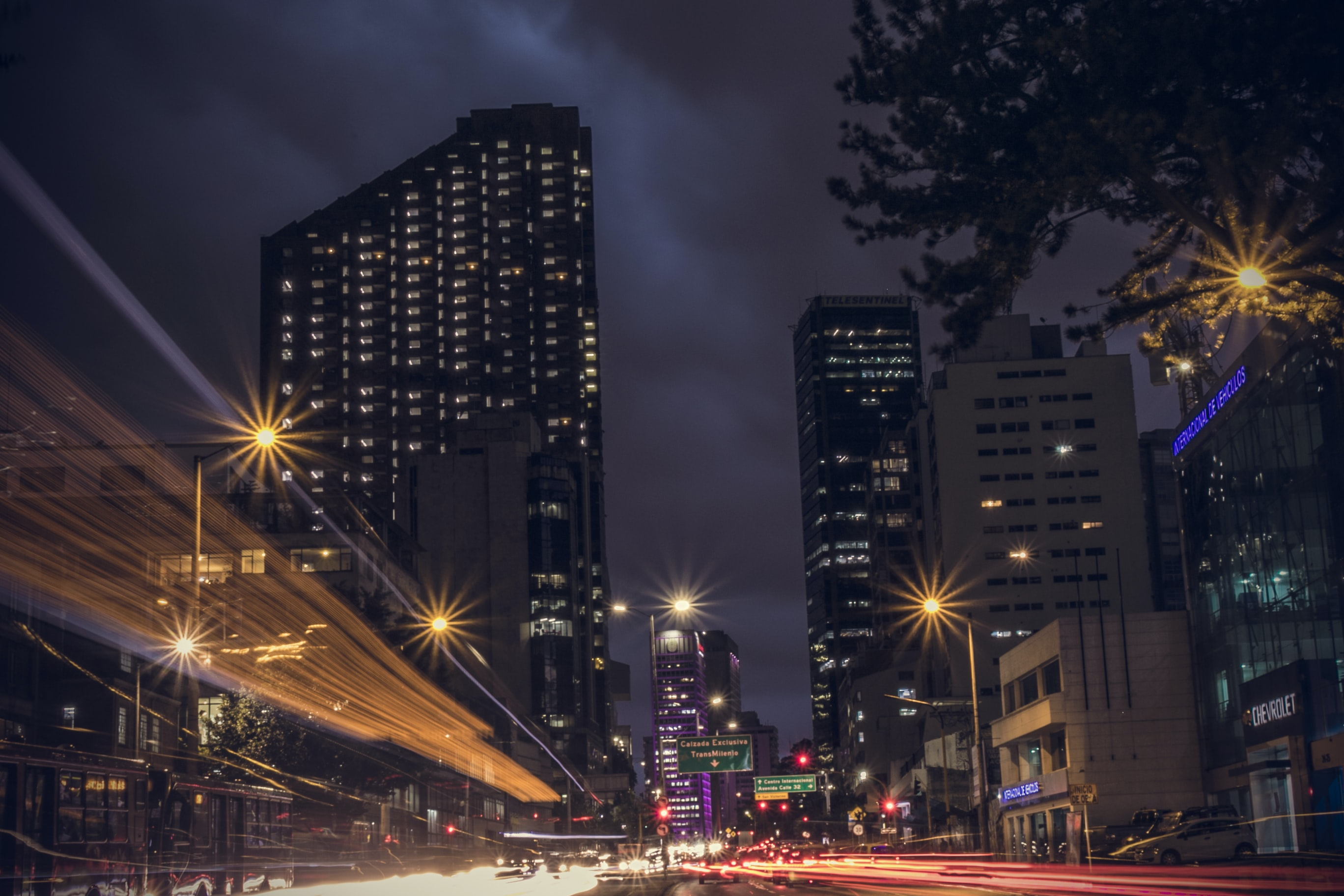 A dark city background featuring large buildings and street light trails in Bogotá