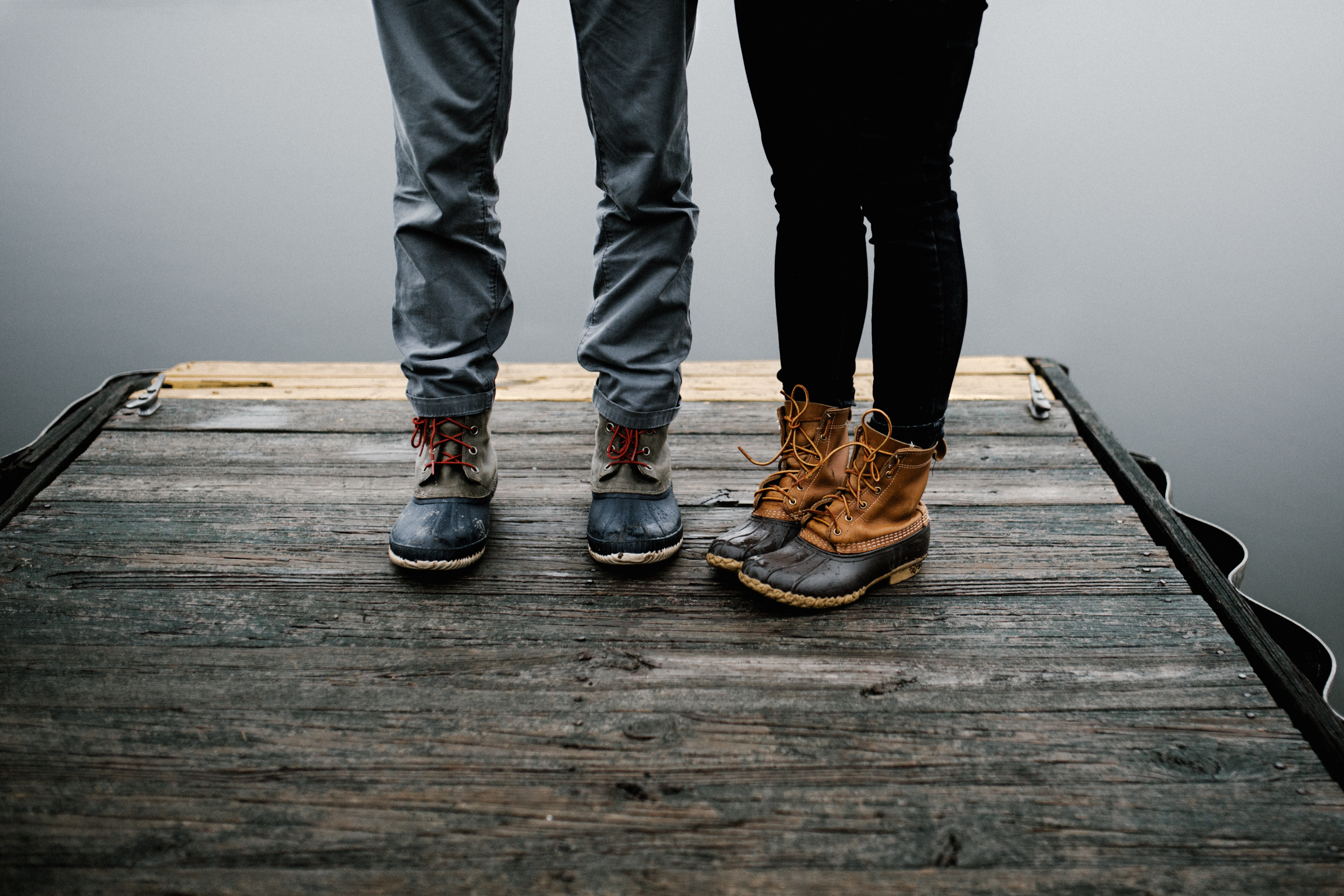 Impermeable shoes worn by a young couple standing on a pier