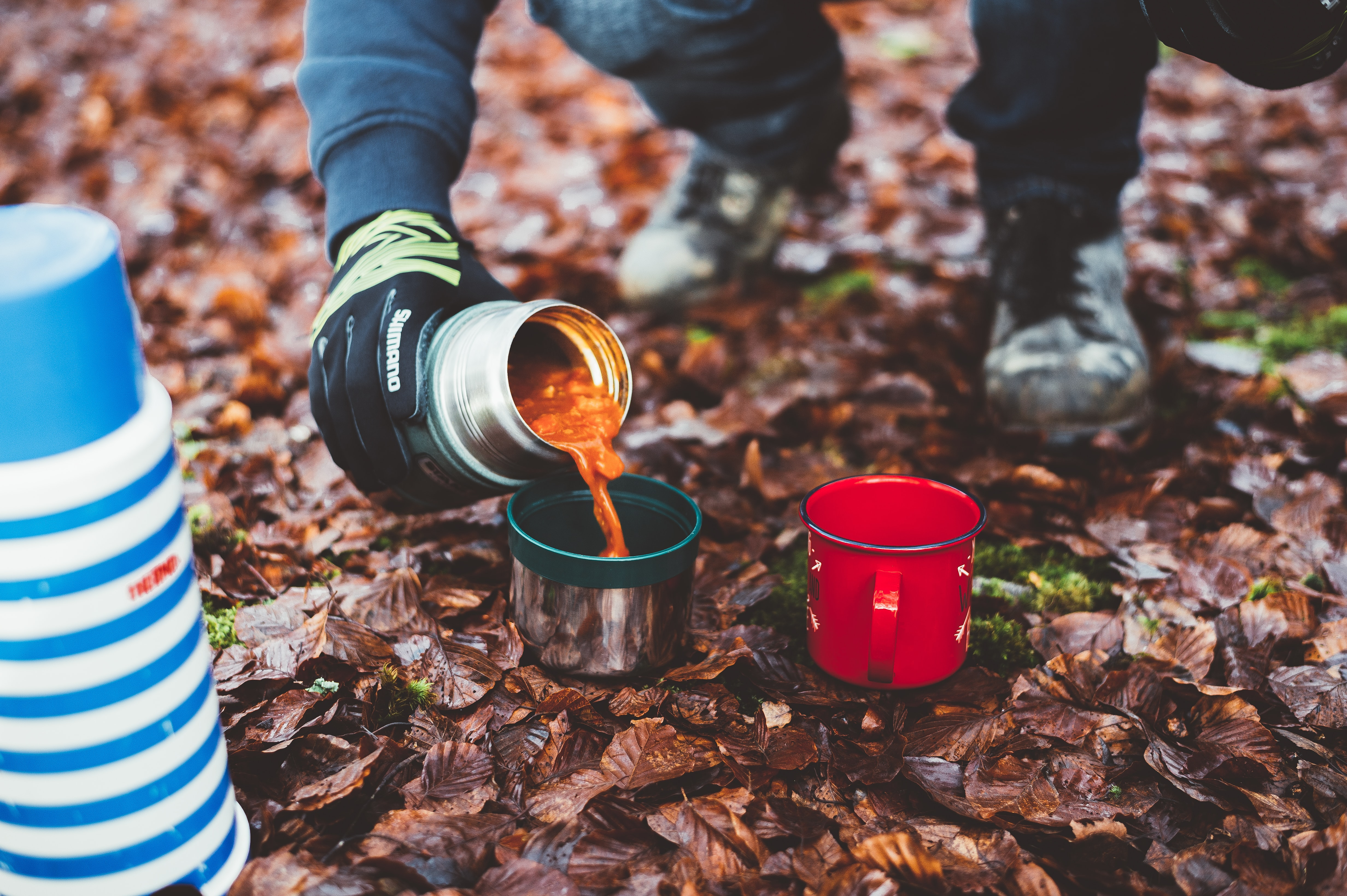 A person pouring soup from a thermos into a cup on the forest floor
