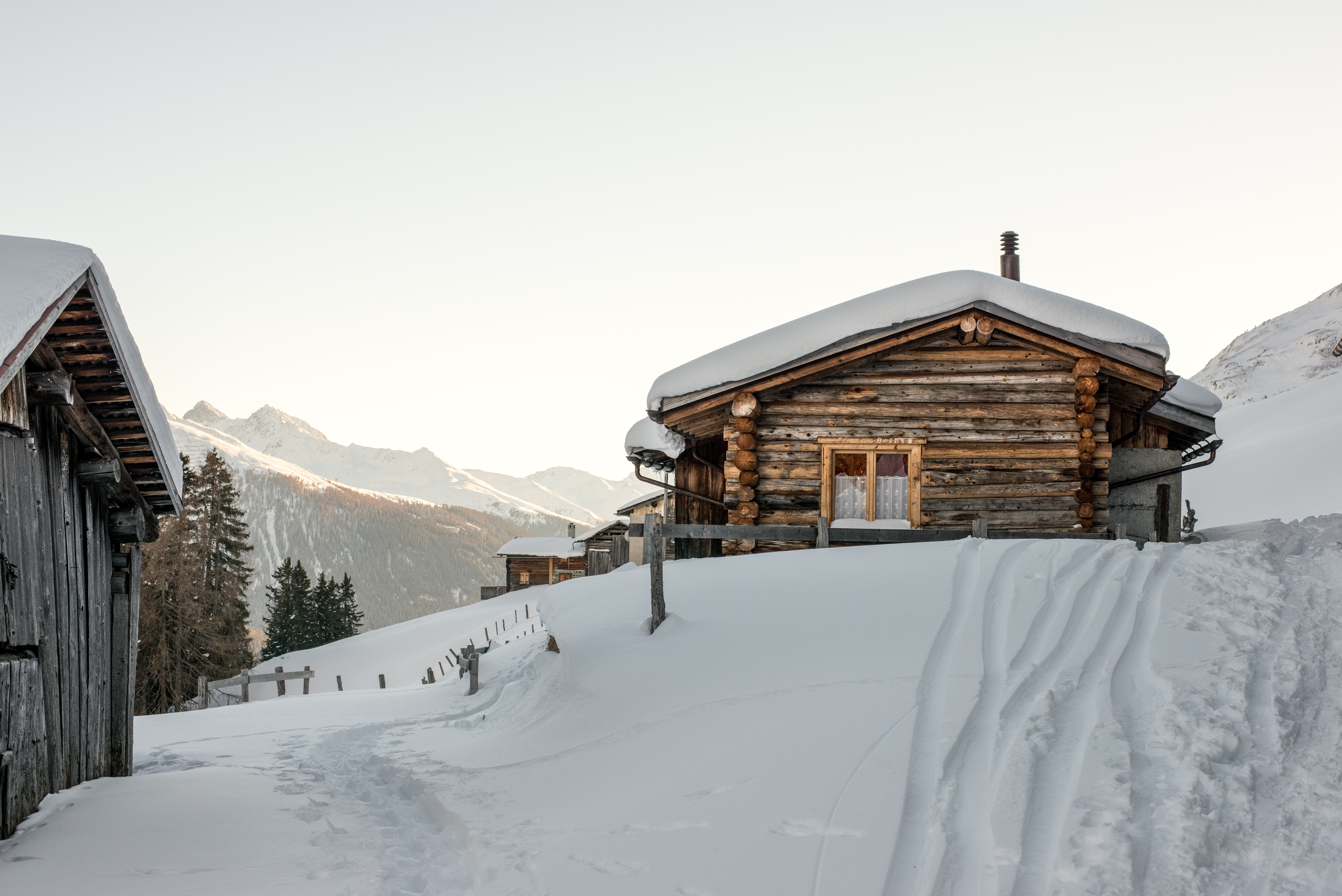 A cottage covered in snow with vehicle tracks at the Klosters Parsenn ski resort