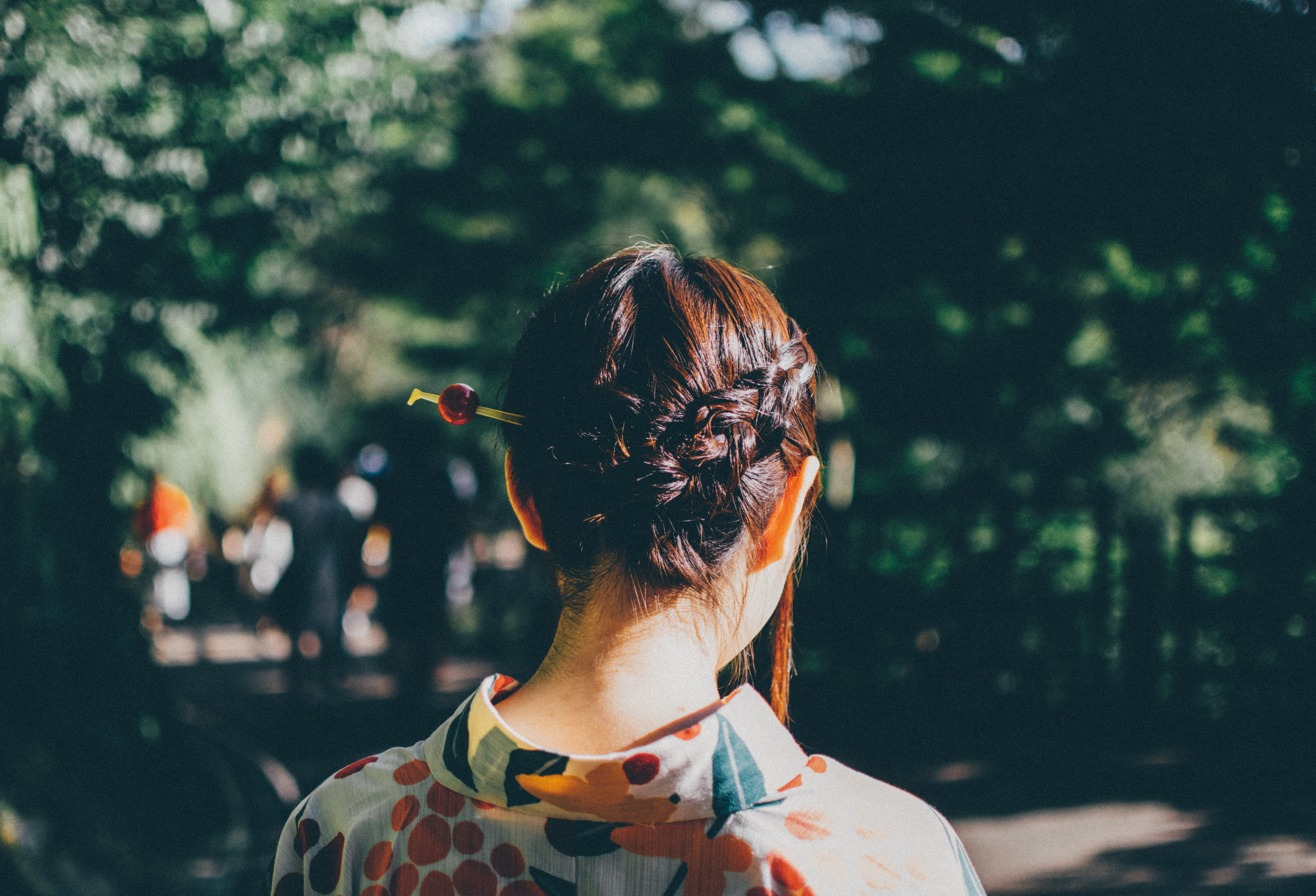 Standing behind a woman with fashionable braided hair in the park