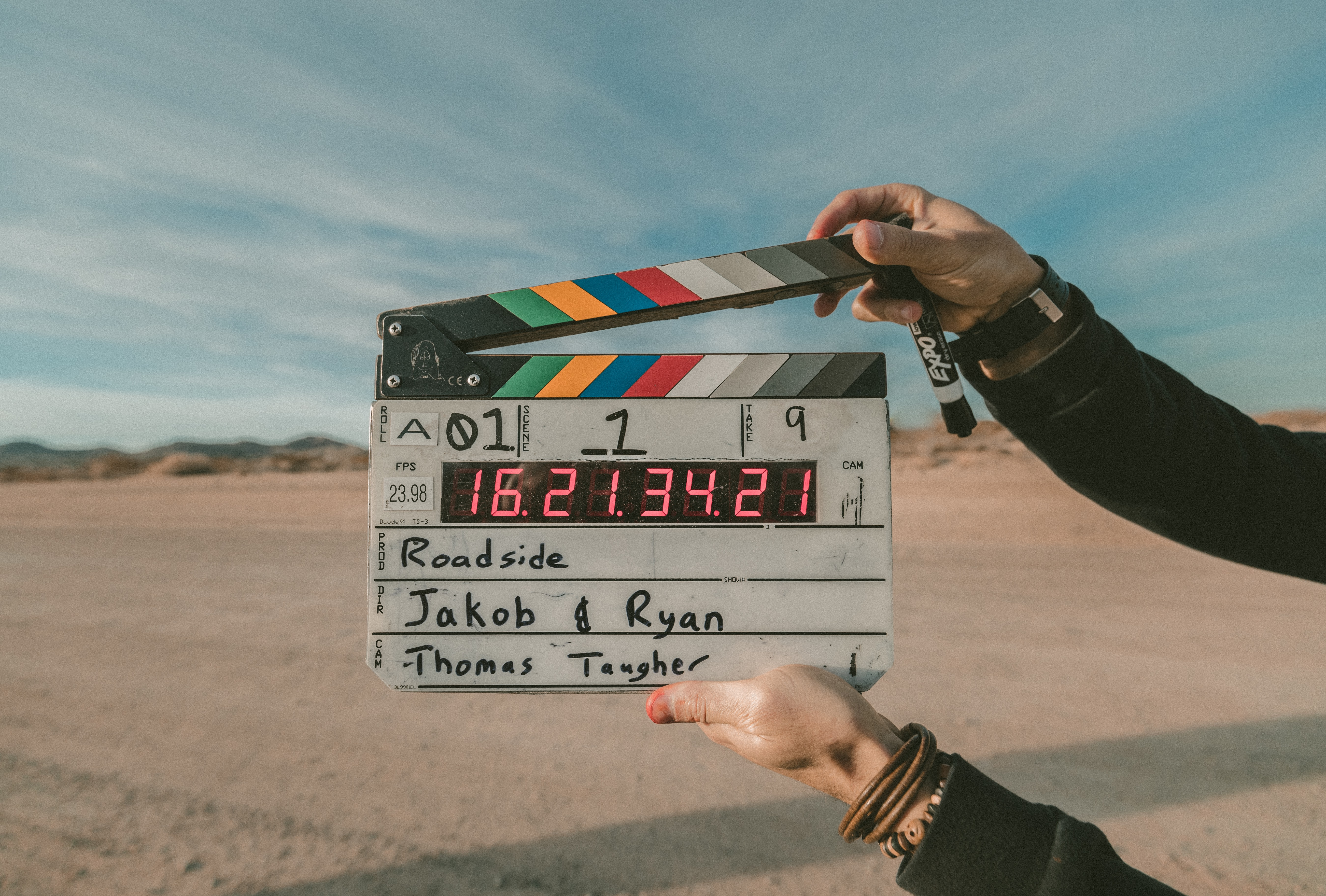 A person holding a clapper board  in a desert