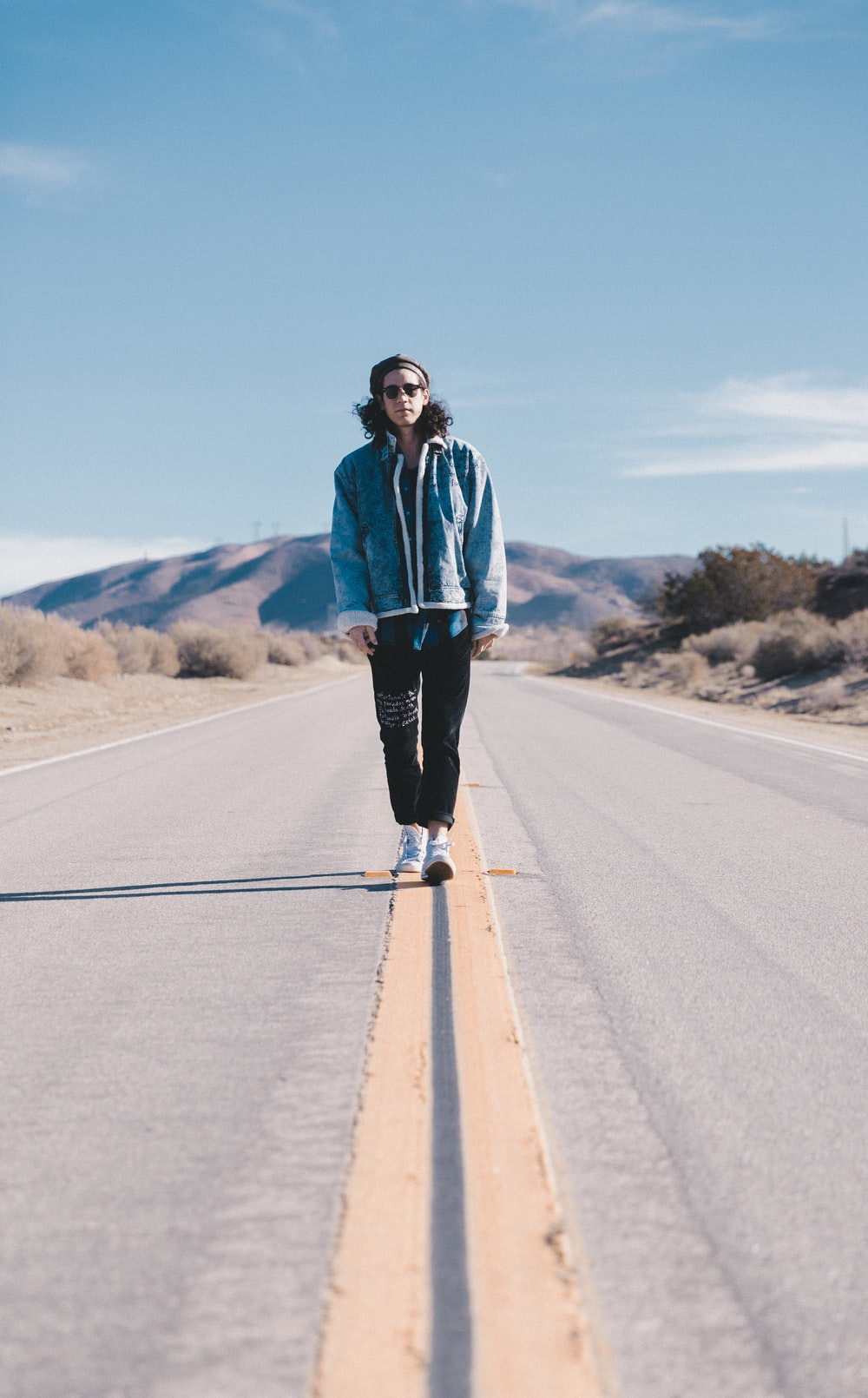man walking in the middle on road at daylight
