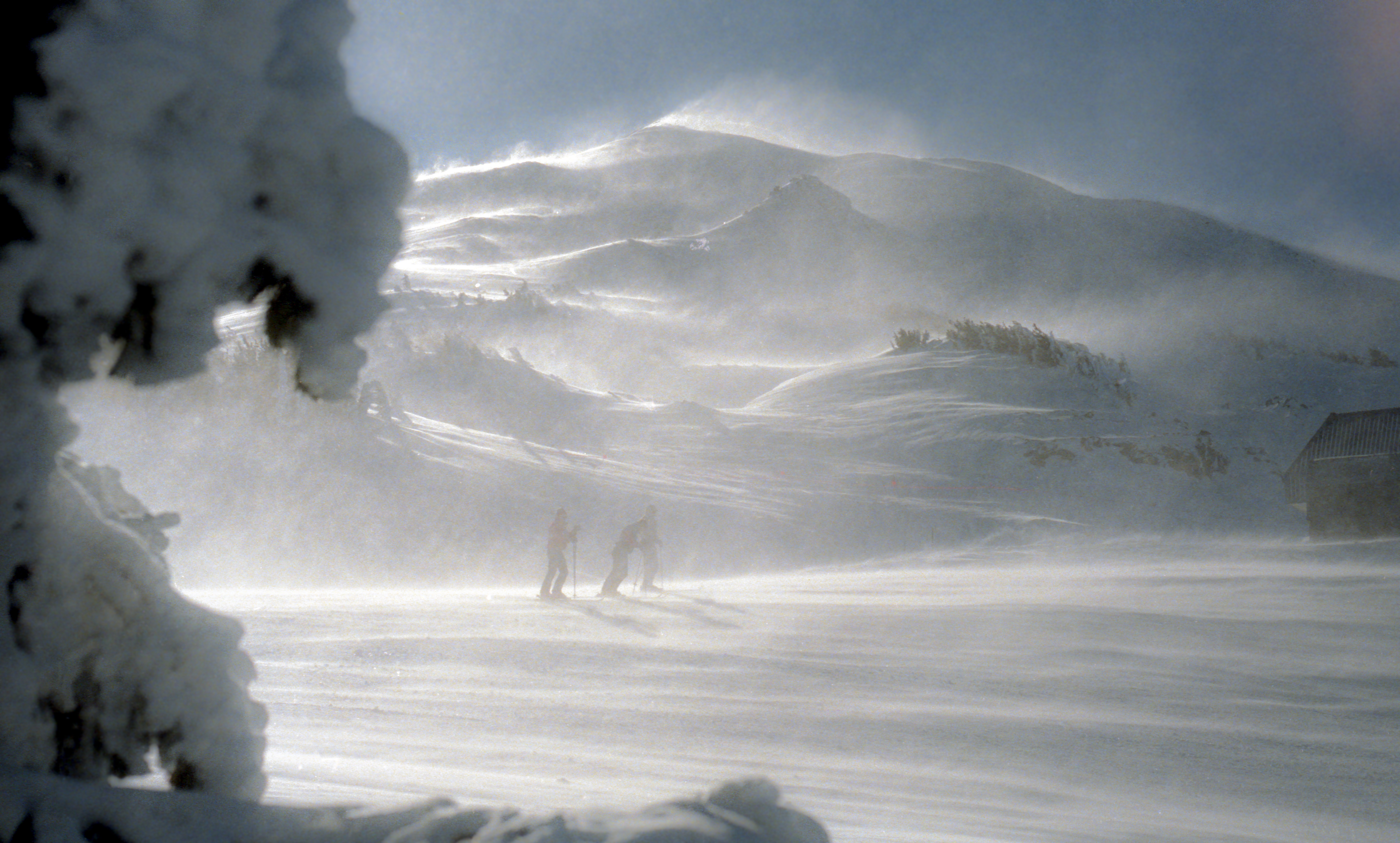 People hiking through windy snow at the bottom of Mount Bachelor in Oregon