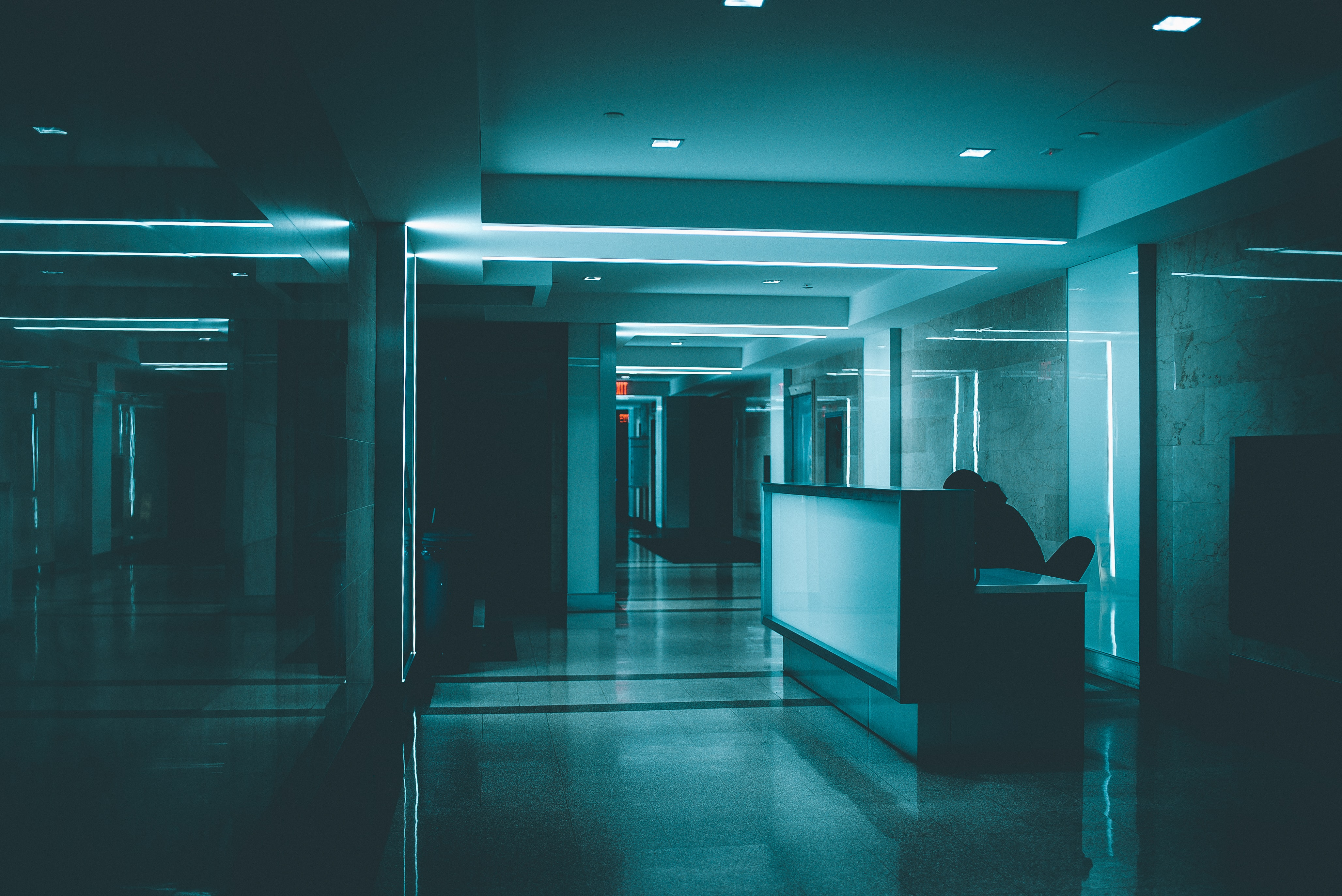A person sits at a desk in a corridor lit by blue light