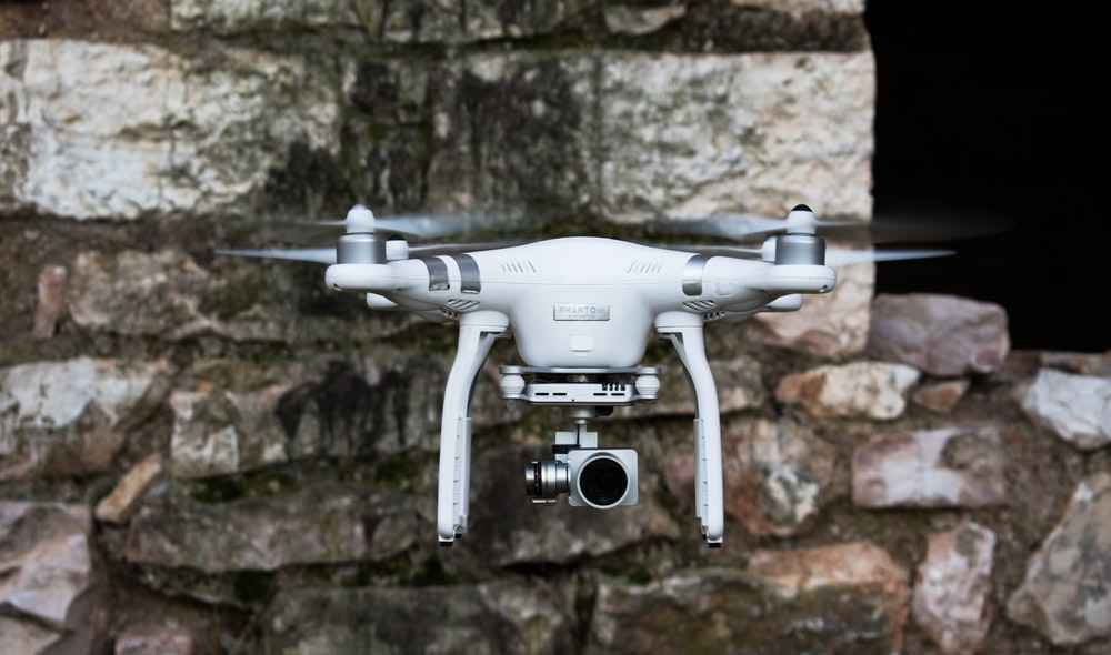Phantom DJI Drone Hovering Beside A Stone Wall
