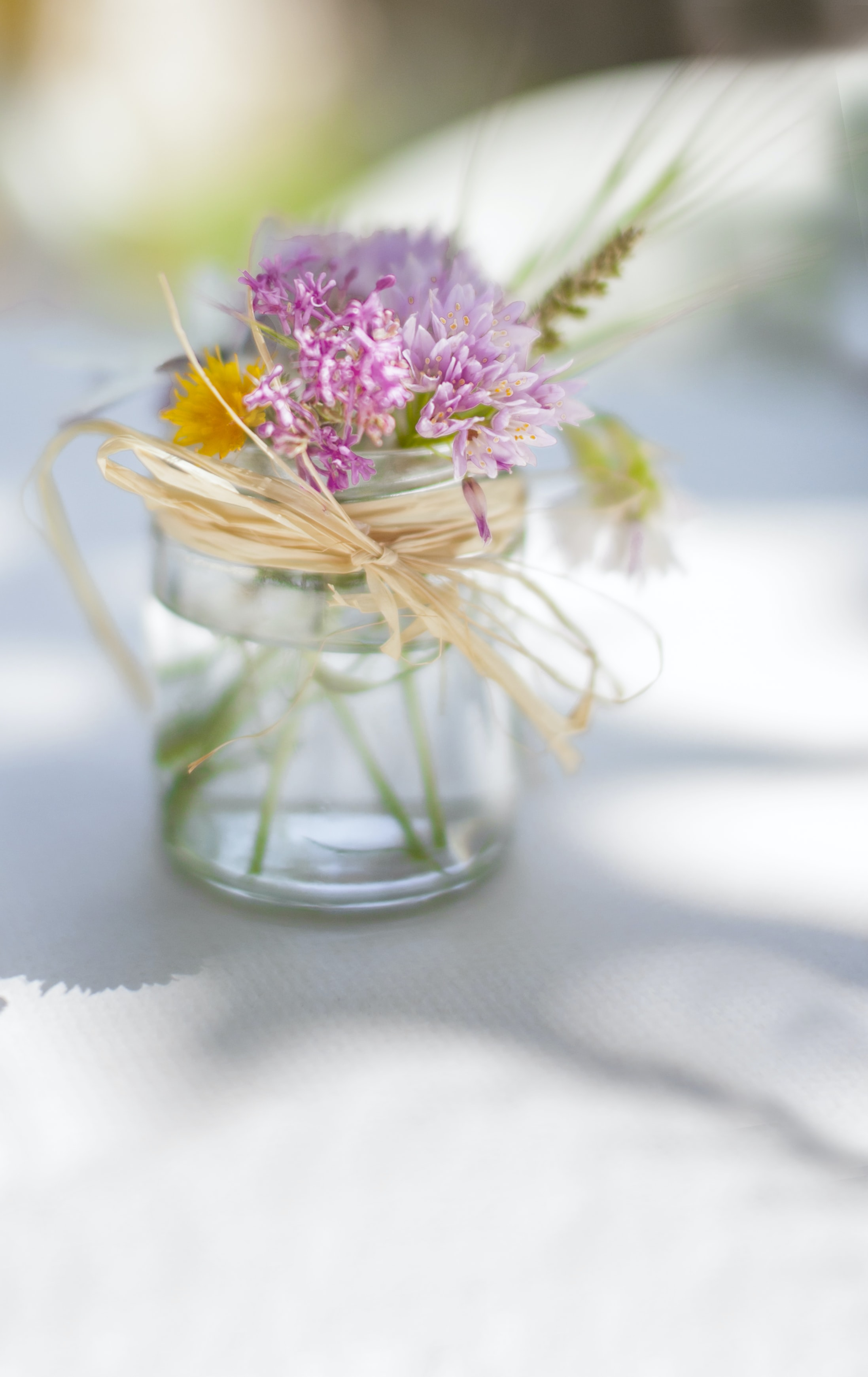 Pink flower in glass jar tied with twine on white table in Spring