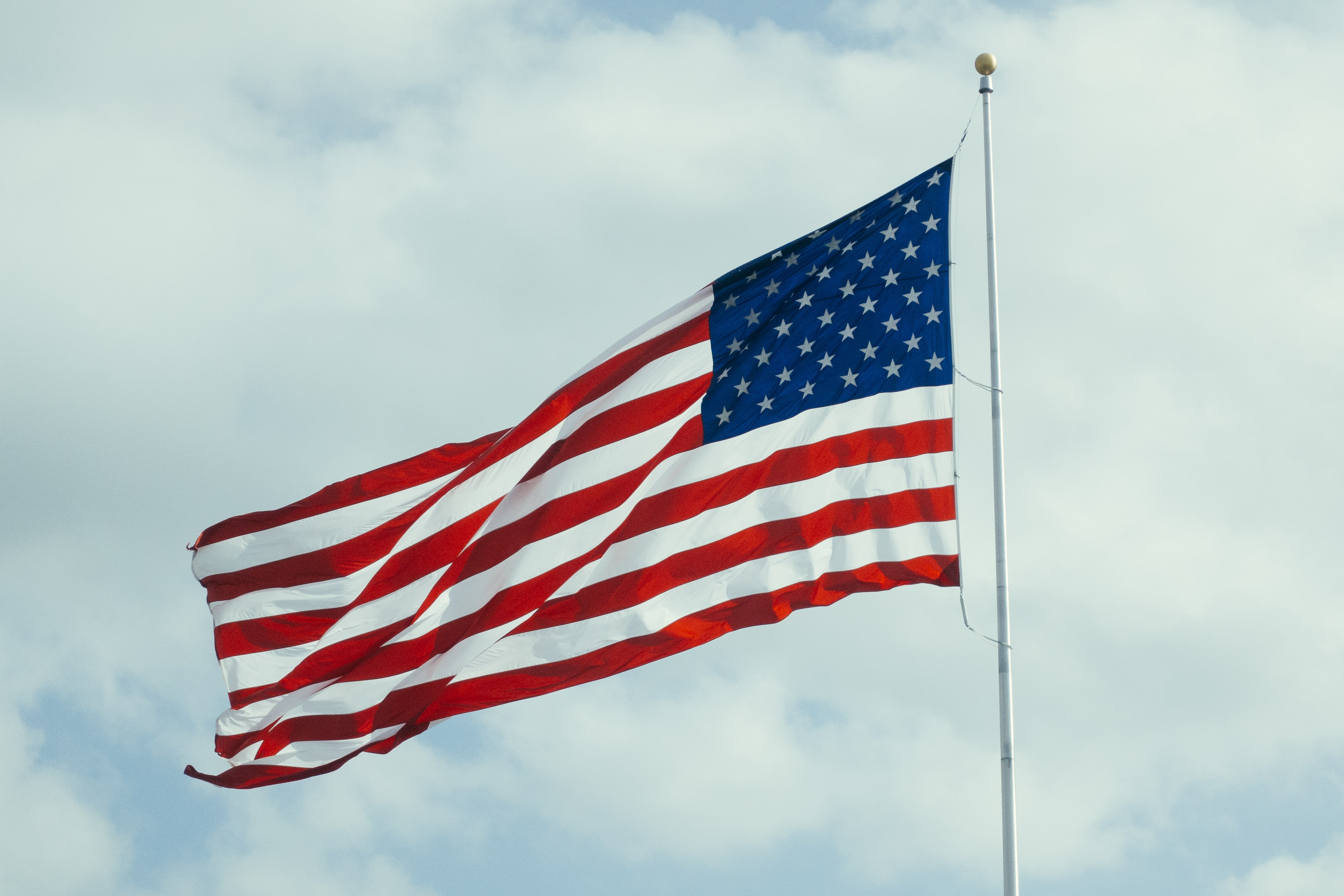 An american flag flaps in the wind on a flagpole