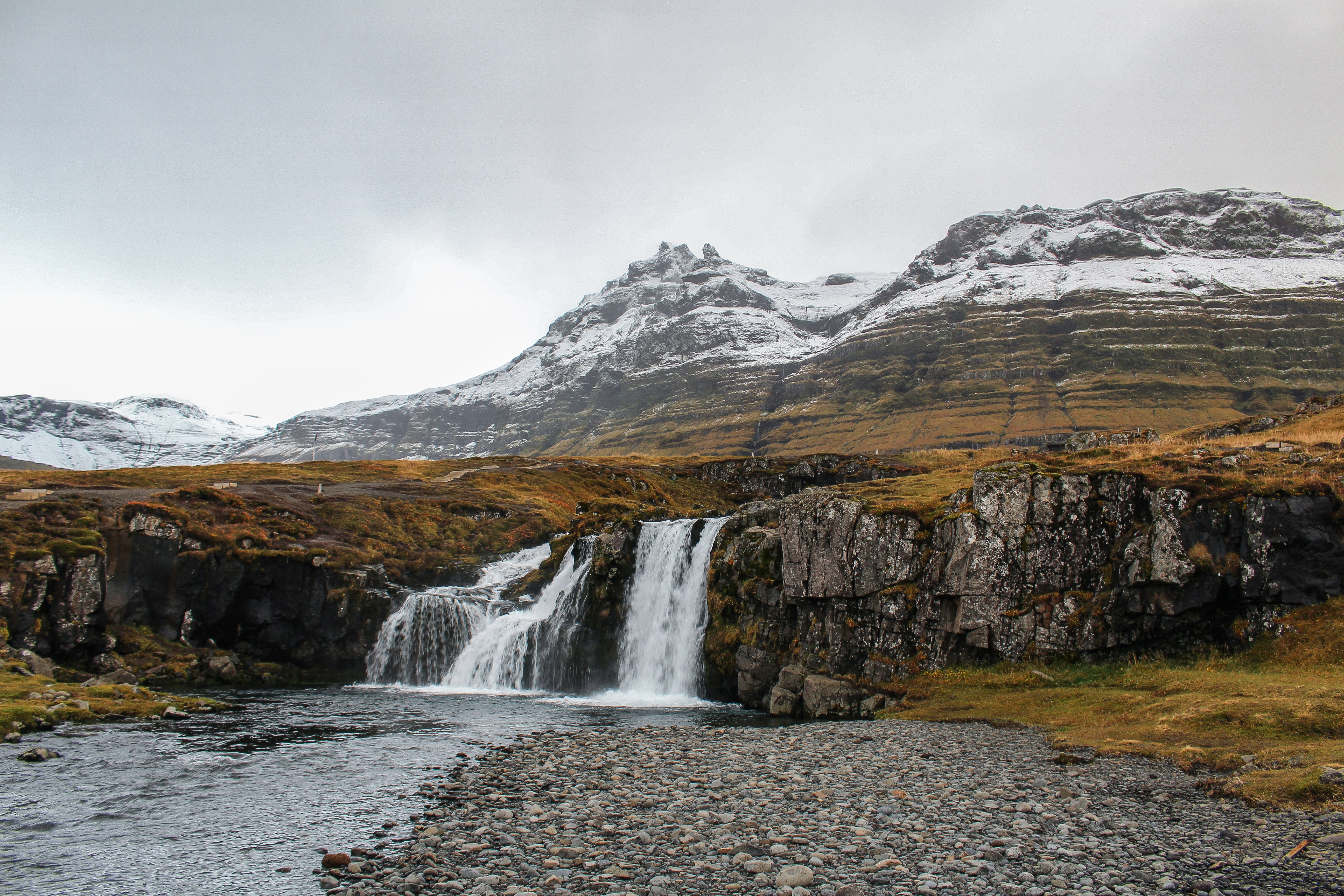 waterfalls and high mountain under cloudy sky