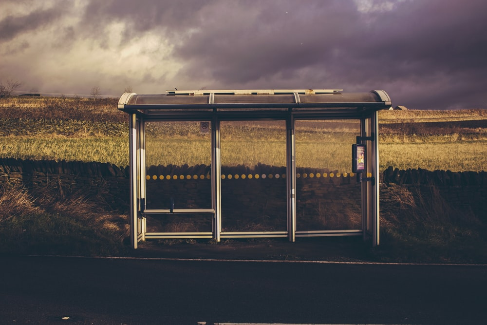 gray and black waiting shed under cloudy sky