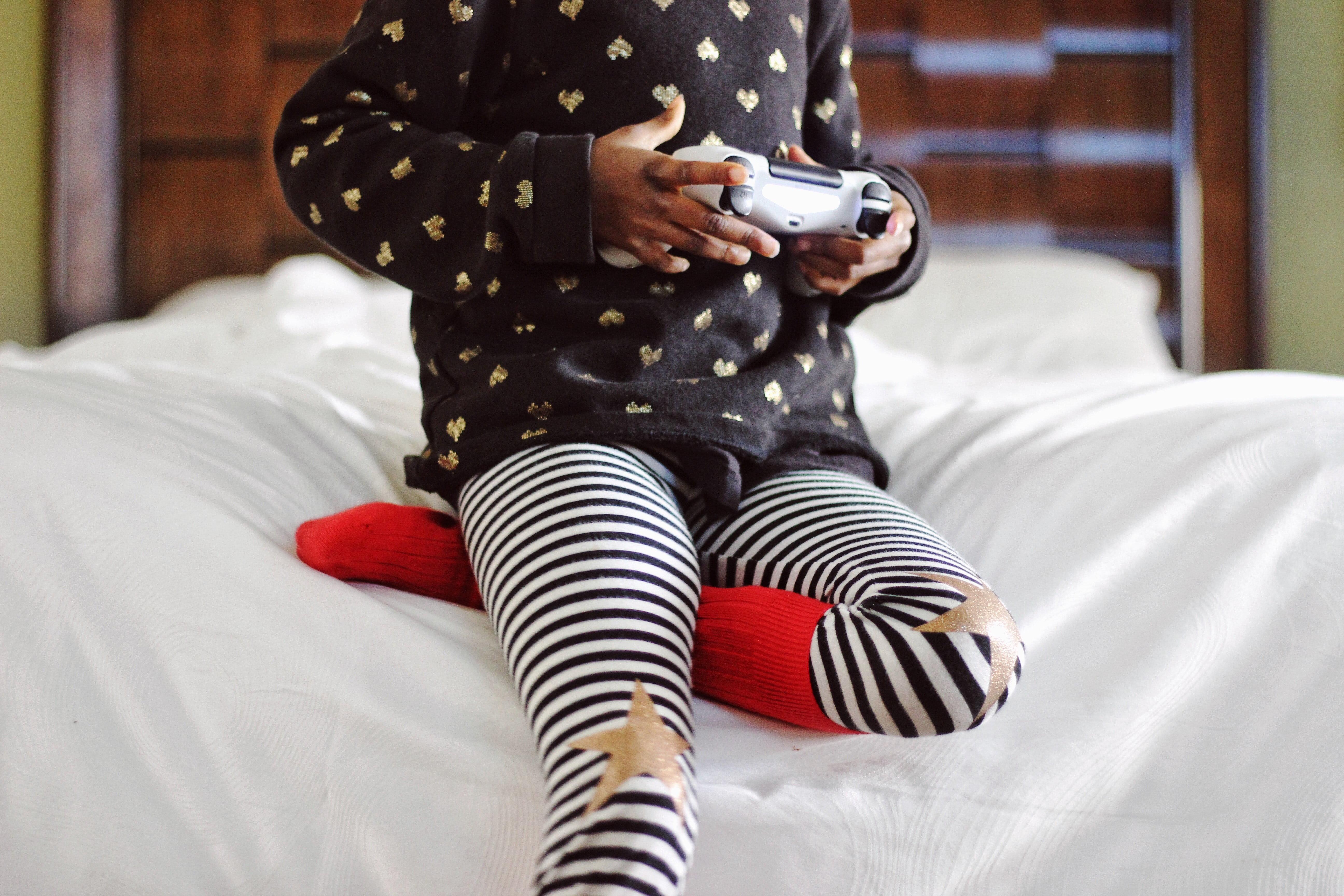 A child in a sweater with a heart pattern holding a white game controller