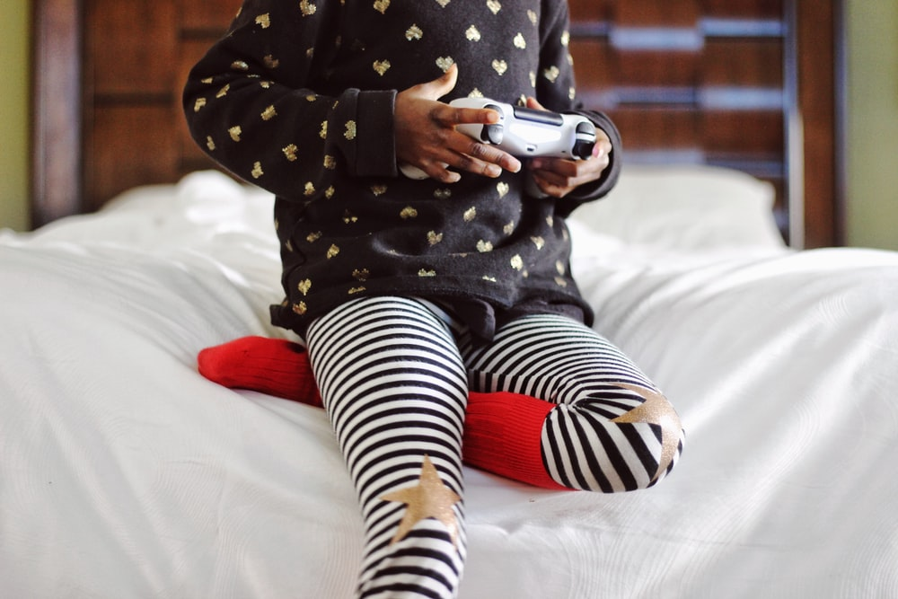 children holding gray game controller sitting on white bed