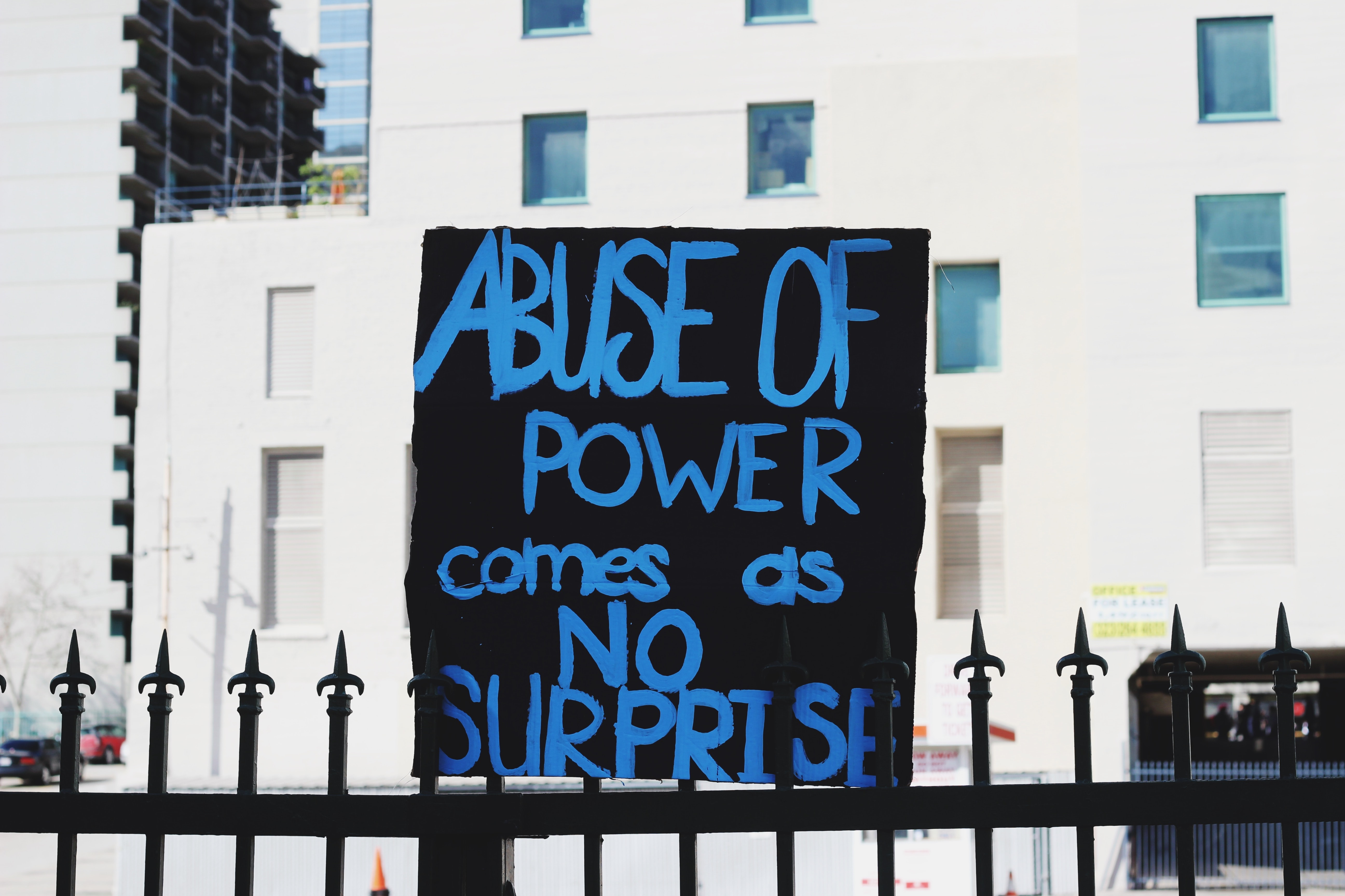 "City Protest sign reads ""abuse of power comes as no surprise"""