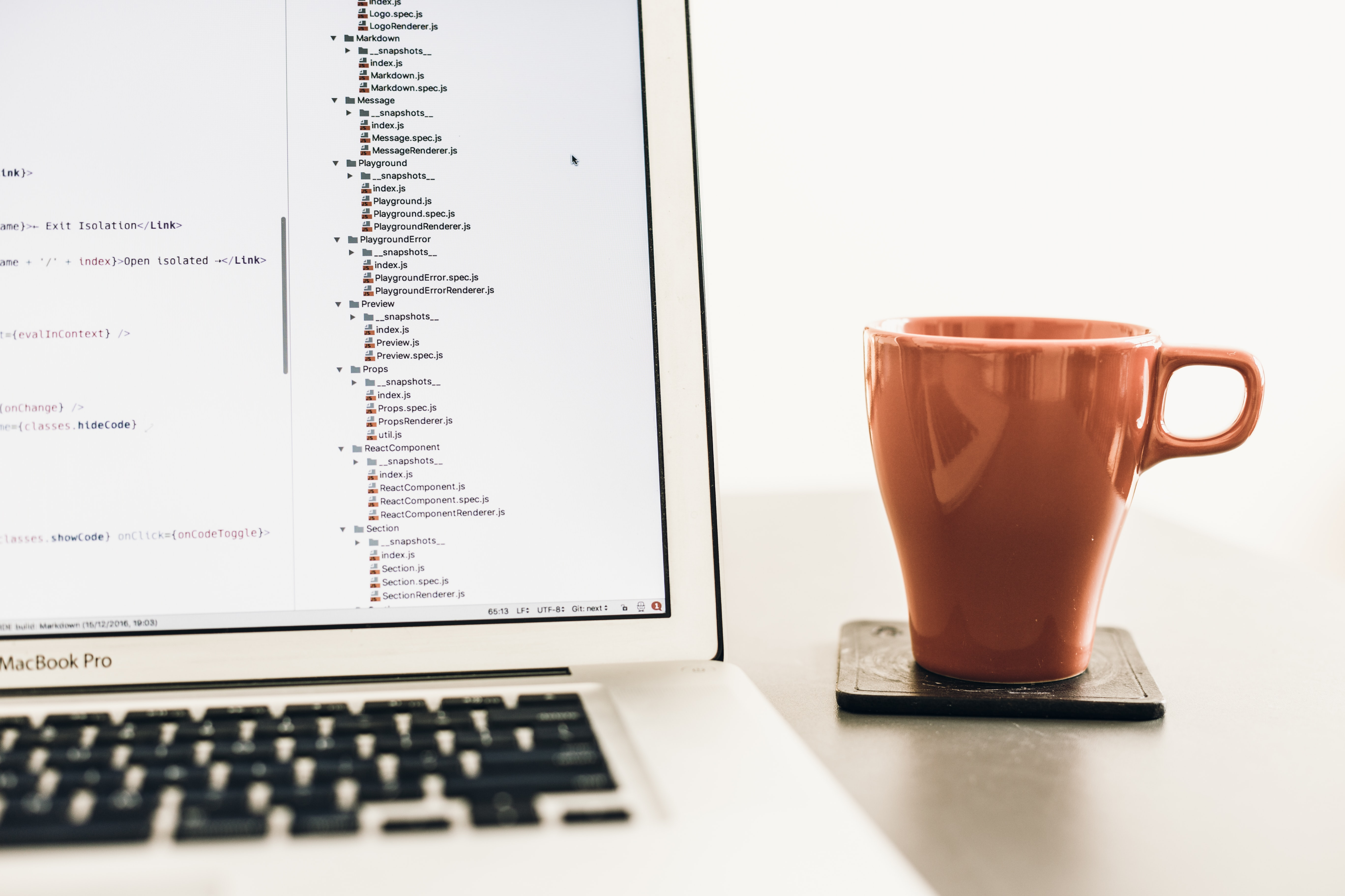 A brown mug next to a MacBook with lines of code on its screen