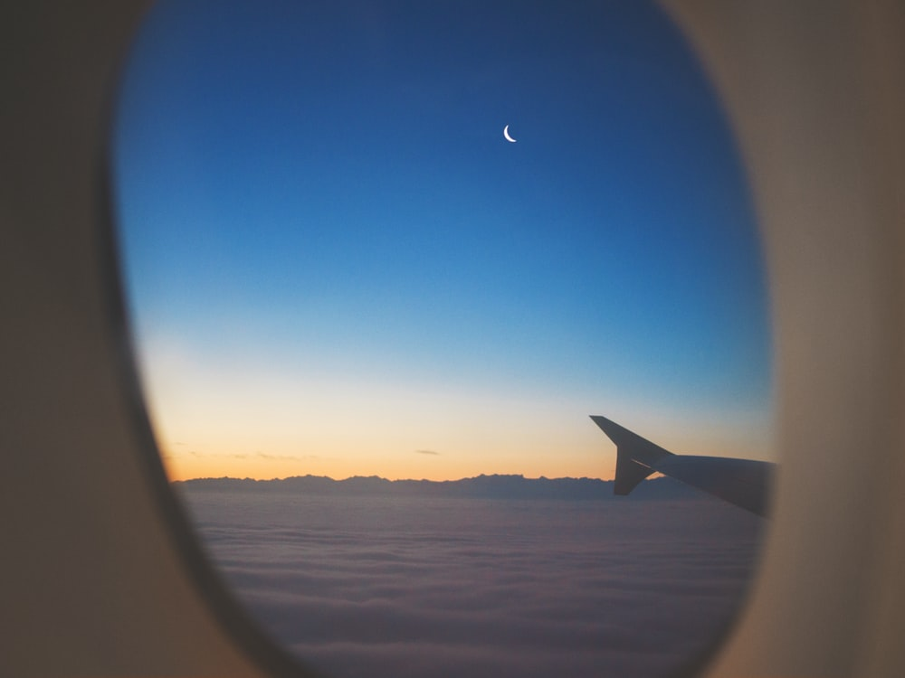 airplane window view of wing, clouds, and half moon