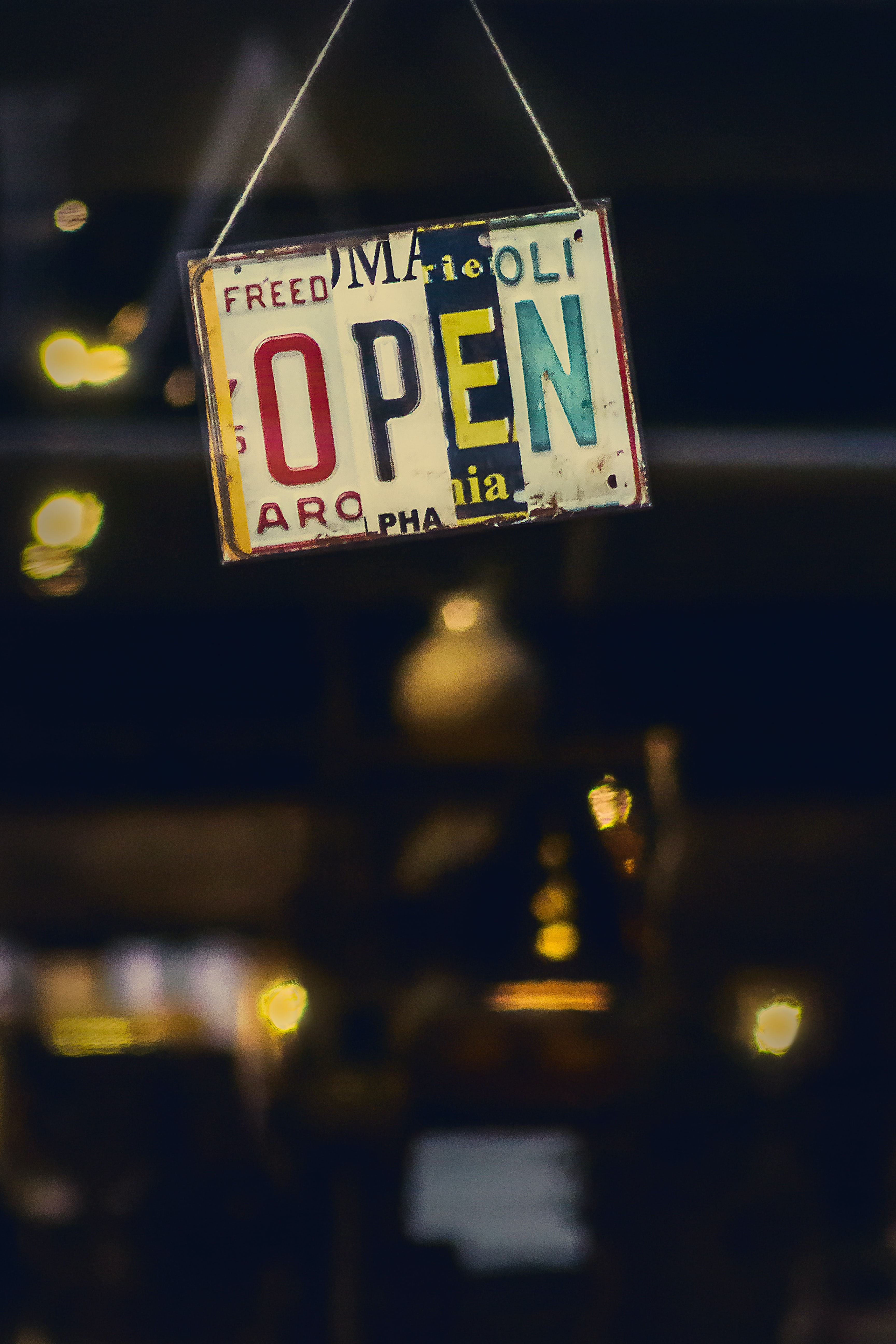 """A colorful """"open"""" sign made from license plates"""