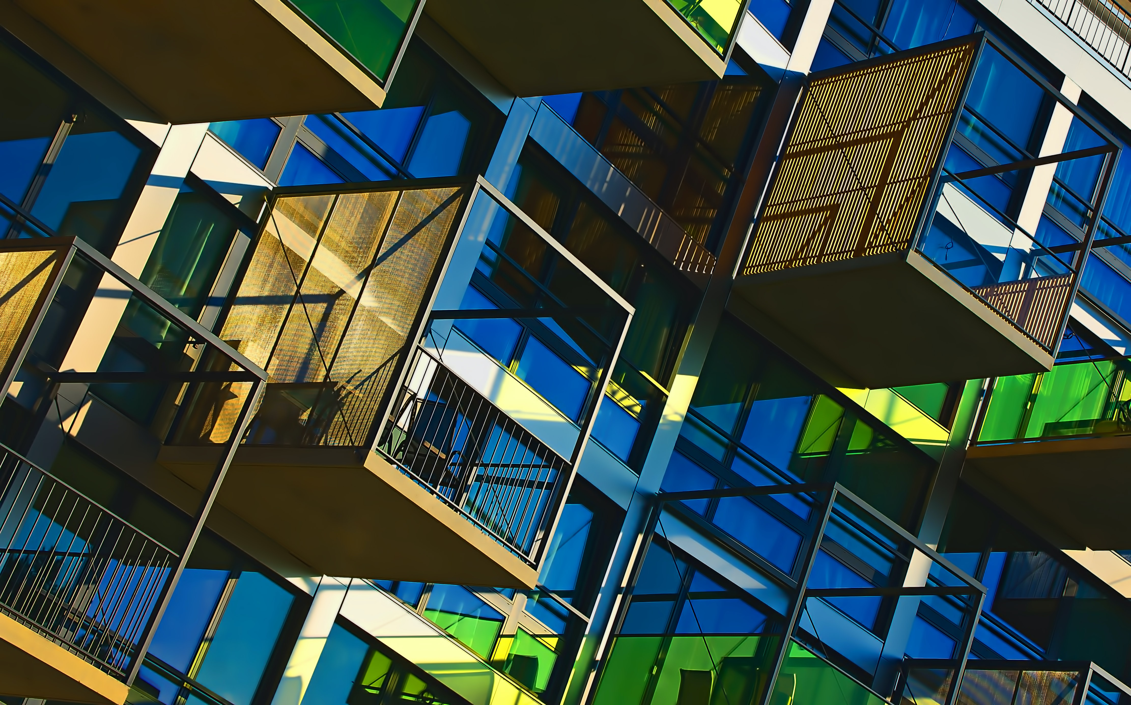 A modern apartment with green and blue windows and extended balconies as seen in Zürich.