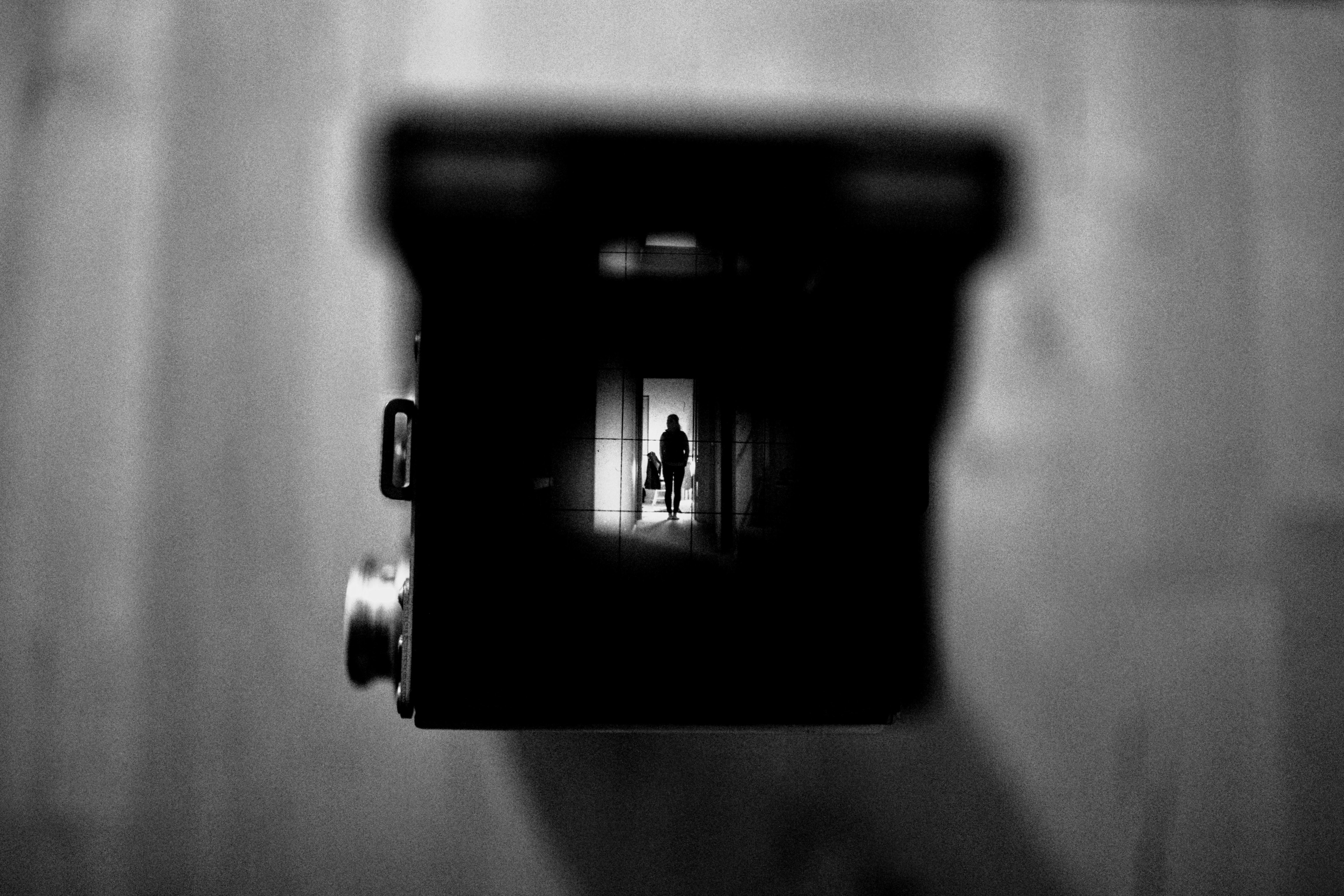 Black and white shot of person in distance through vintage camera viewfinder, Willoughby
