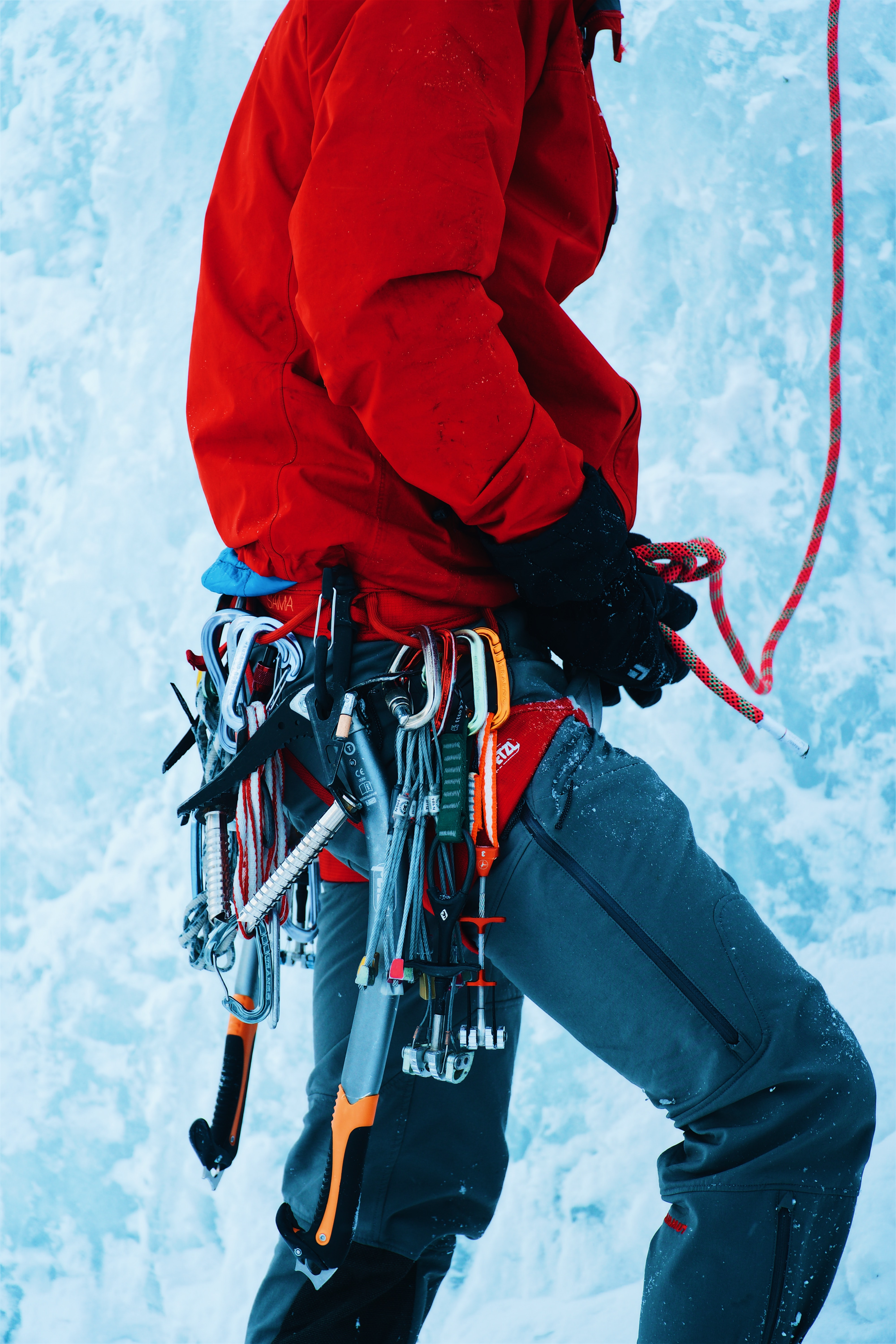A person with ice climbing gear strapped to a harness on an ice wall