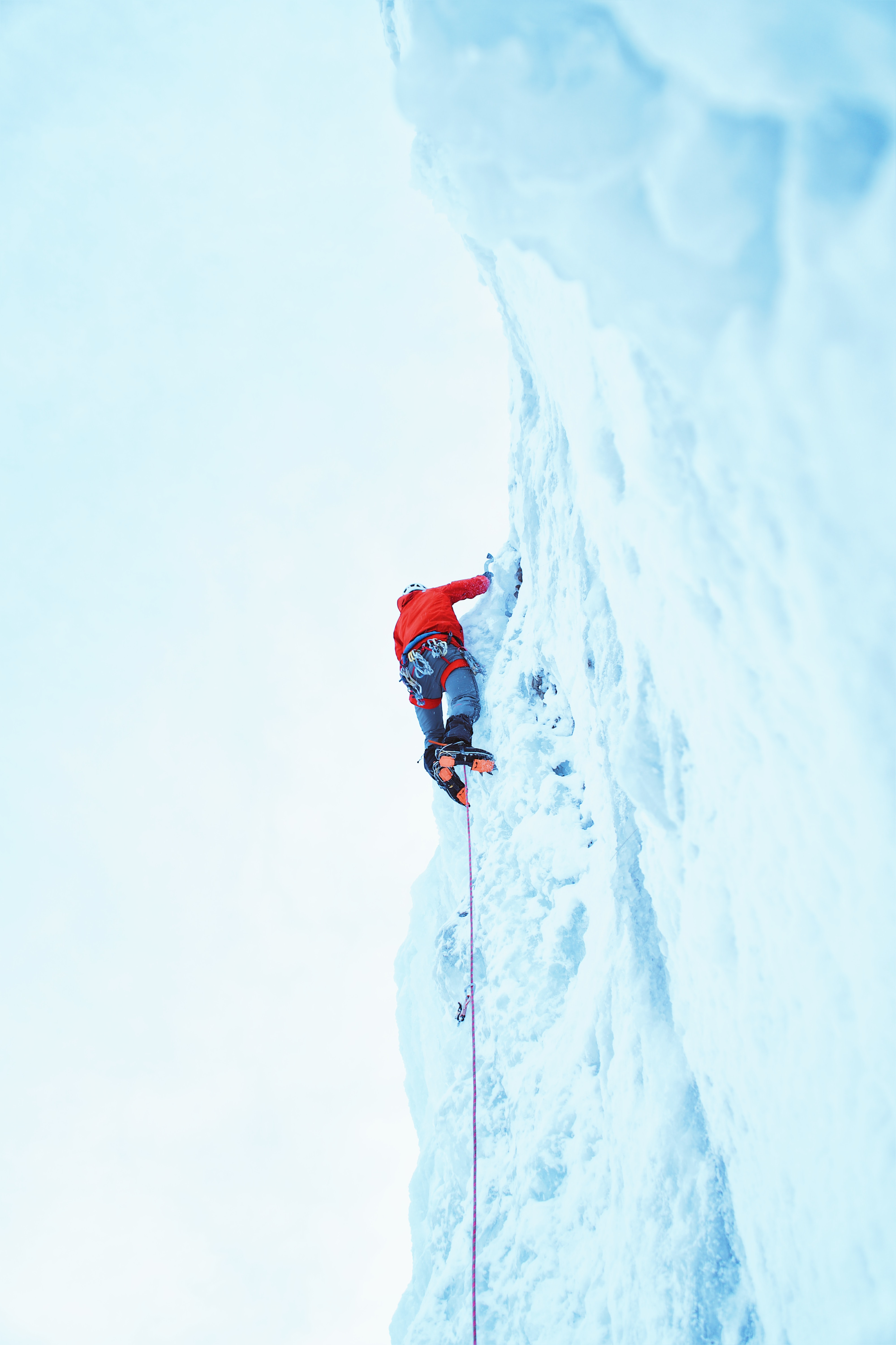 A person wearing a red shirt ice climbing, attached to a rope, at Bridal Veil Falls