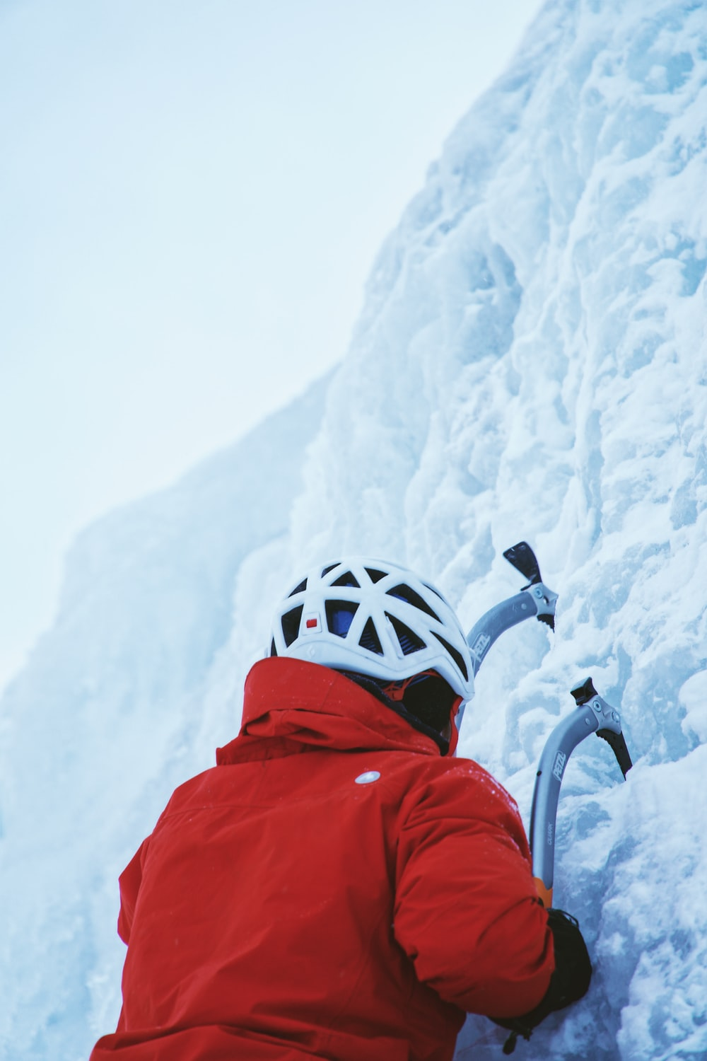 person in red jacket while climbing ice wall at daytime