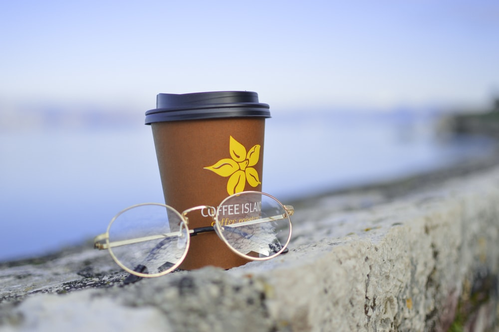 gold-colored framed eyeglasses beside plastic disposable cup