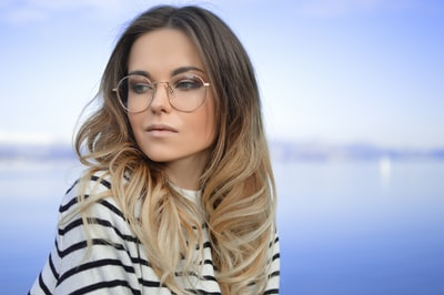 woman wearing black and white striped top and round eyeglasses