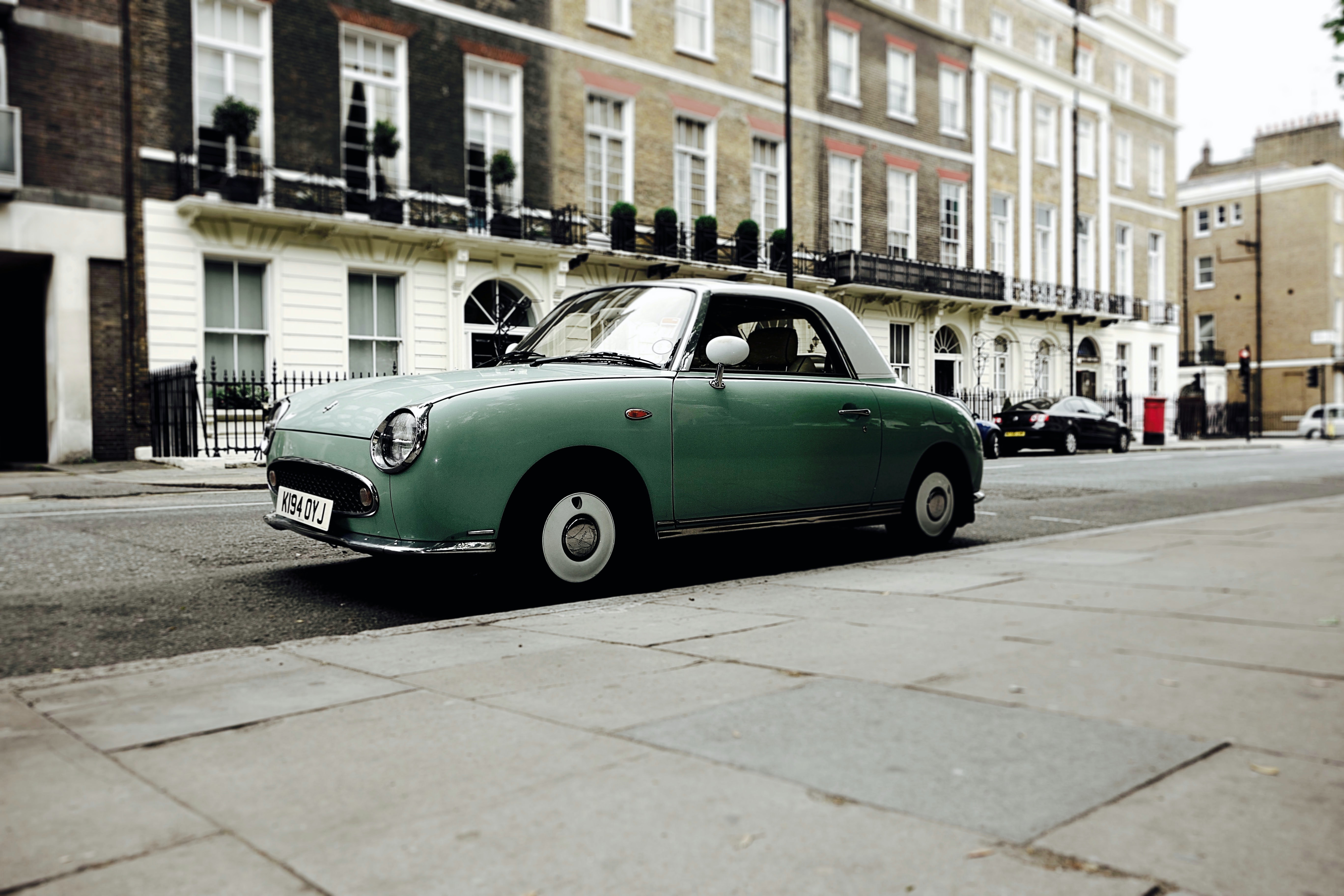 Green vintage car parked on the streets of a European neighborhood