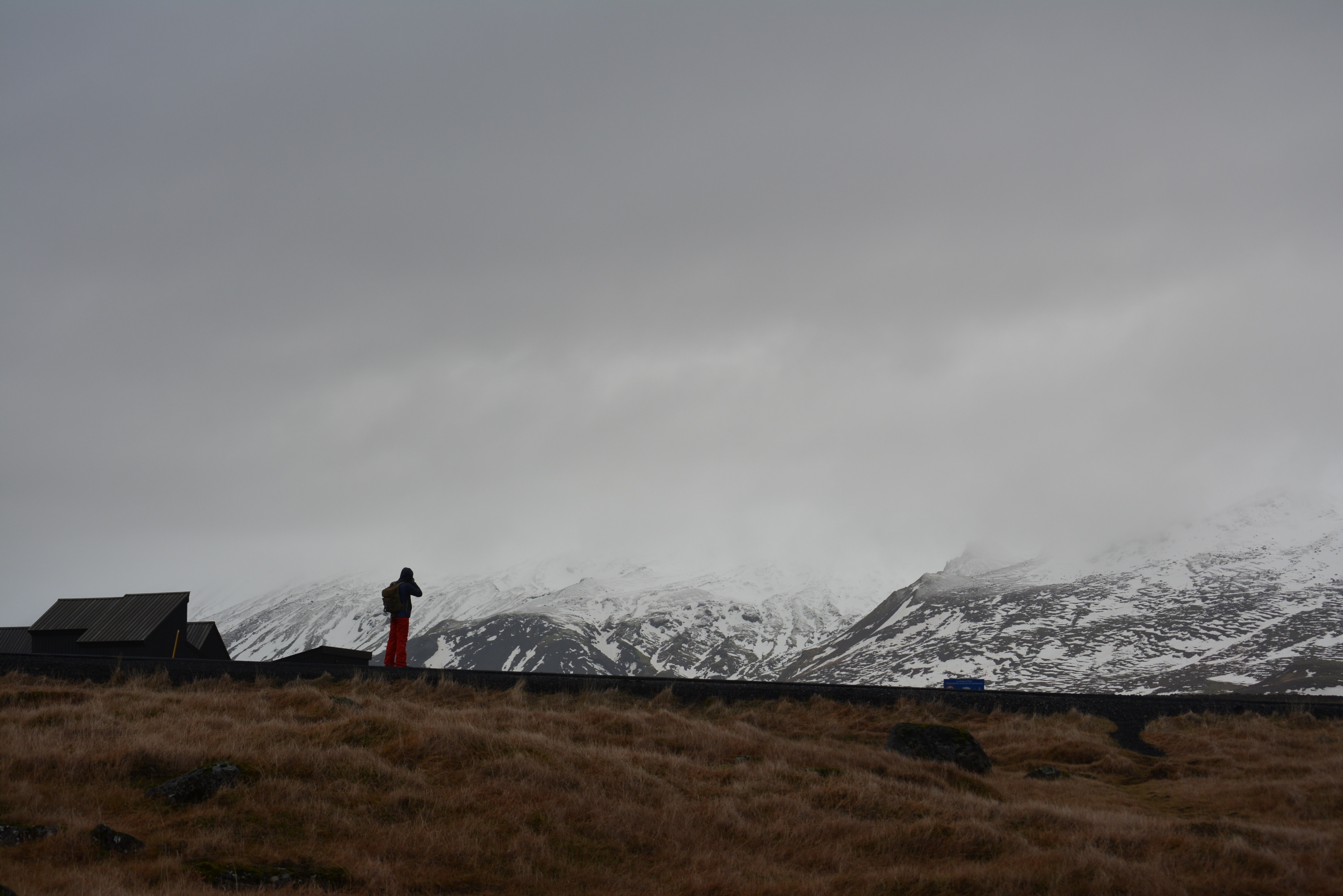 A person stands outside of a building, gazing at the snow capped mountains in Hellnar, Iceland