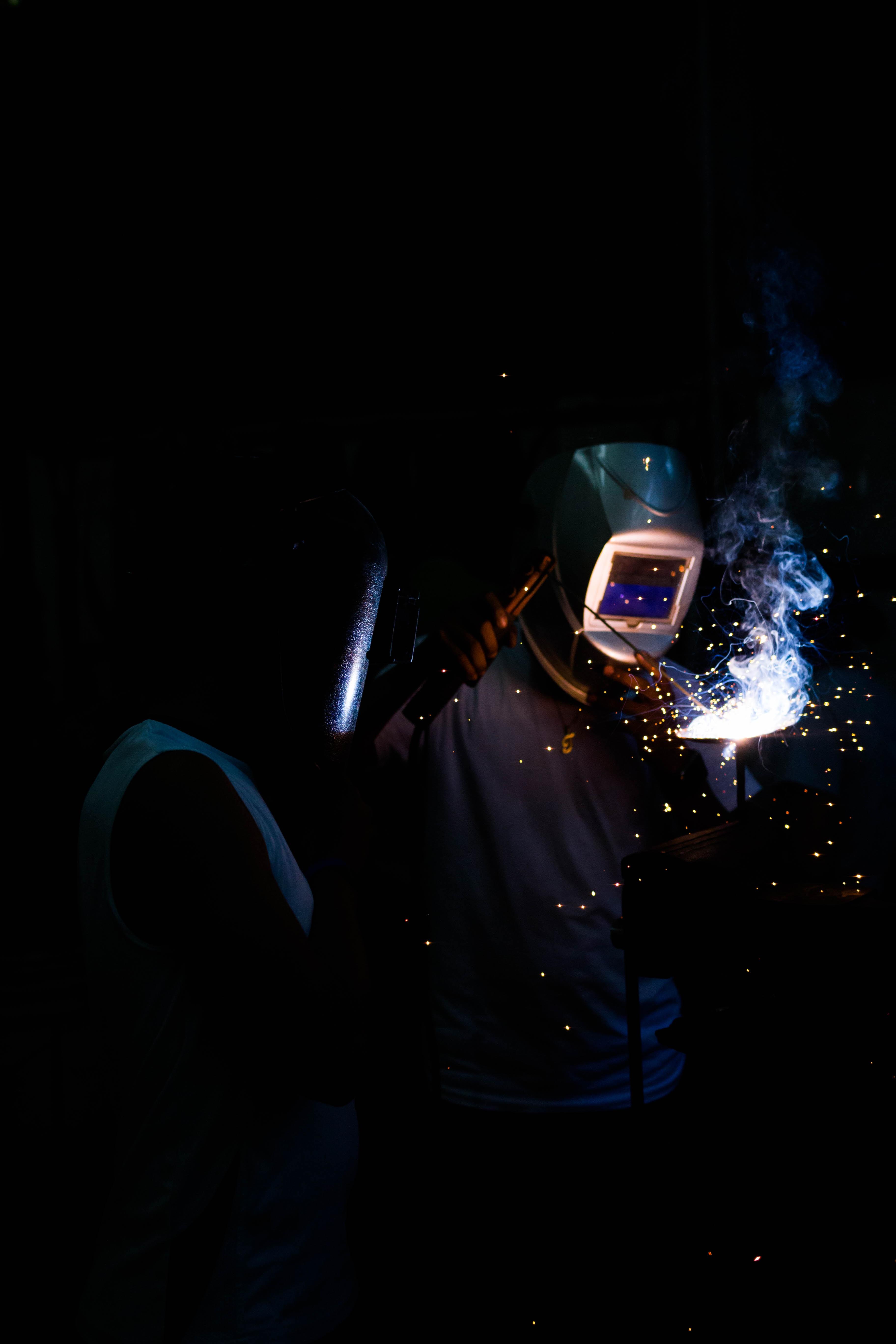 Two people weld in the dark in Nejapa