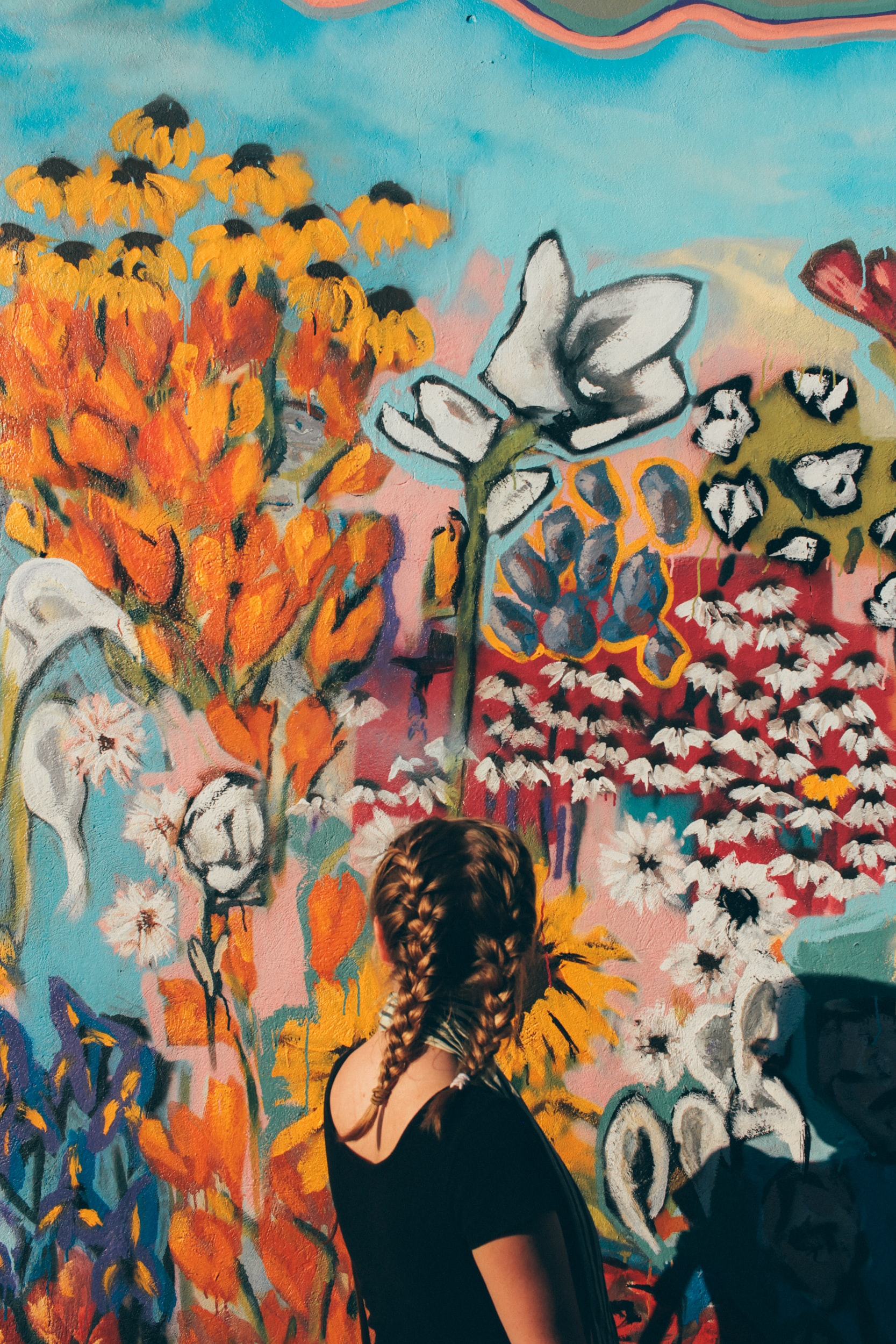 woman facing in front of floral graffiti wall