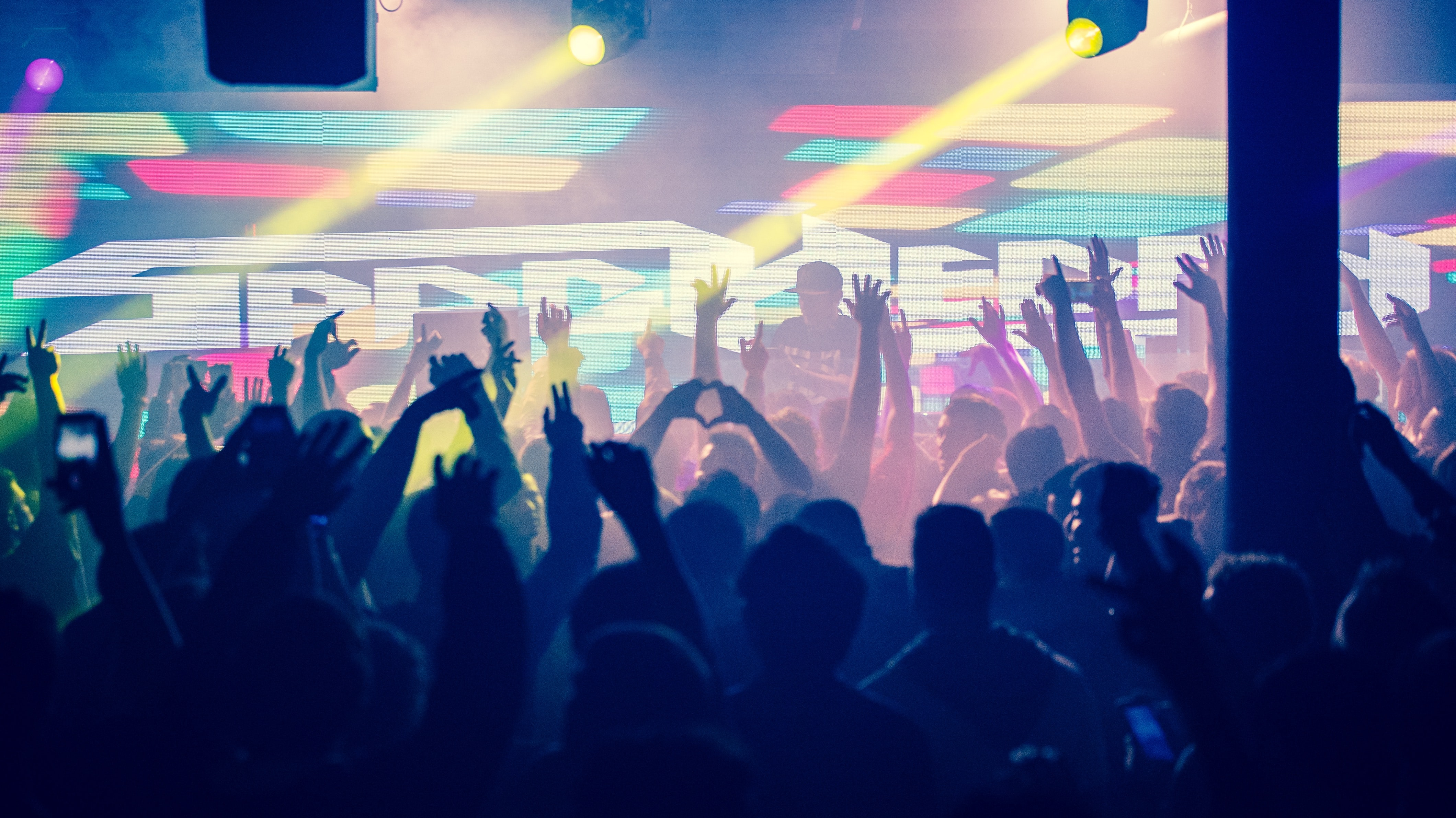 Crowd with raised arms in a colorful club in silhouette
