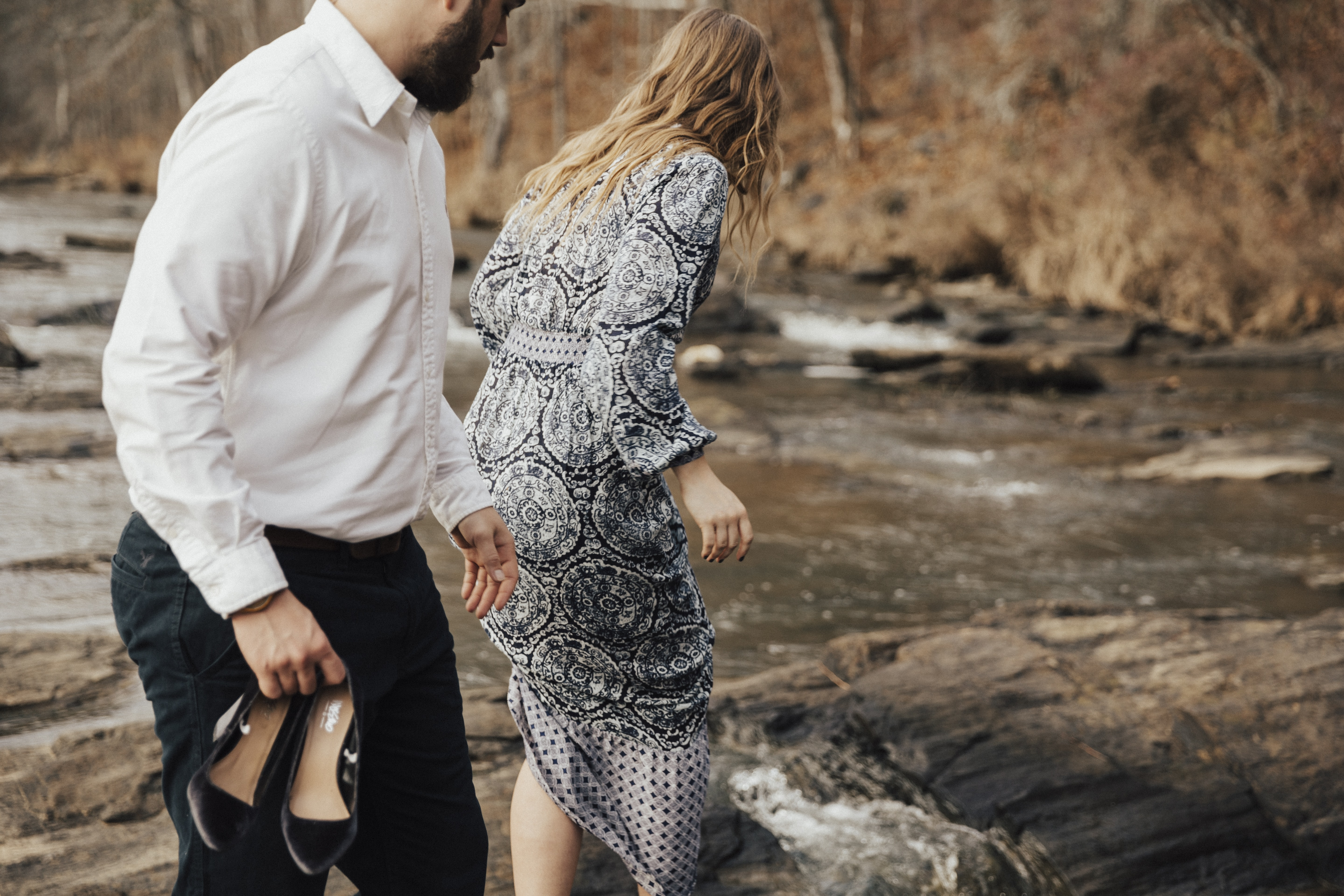 A couple in formal clothing removes their shoes to wade in a rocky stream