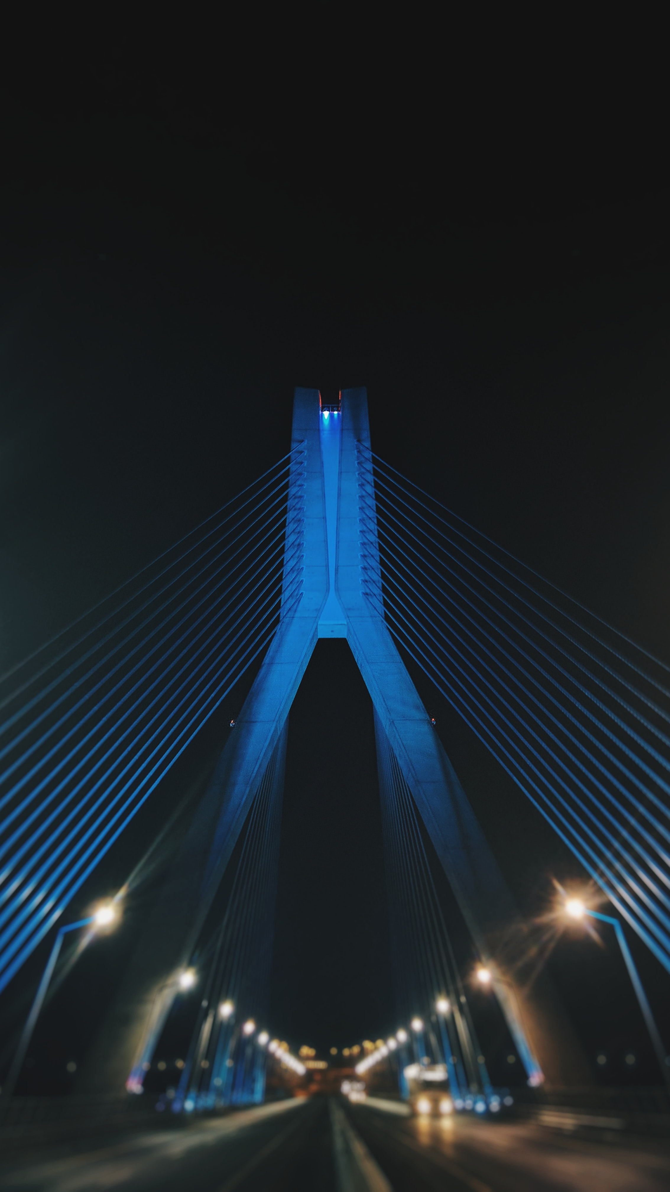 A blue illuminated bridge at night across a street full of lanterns