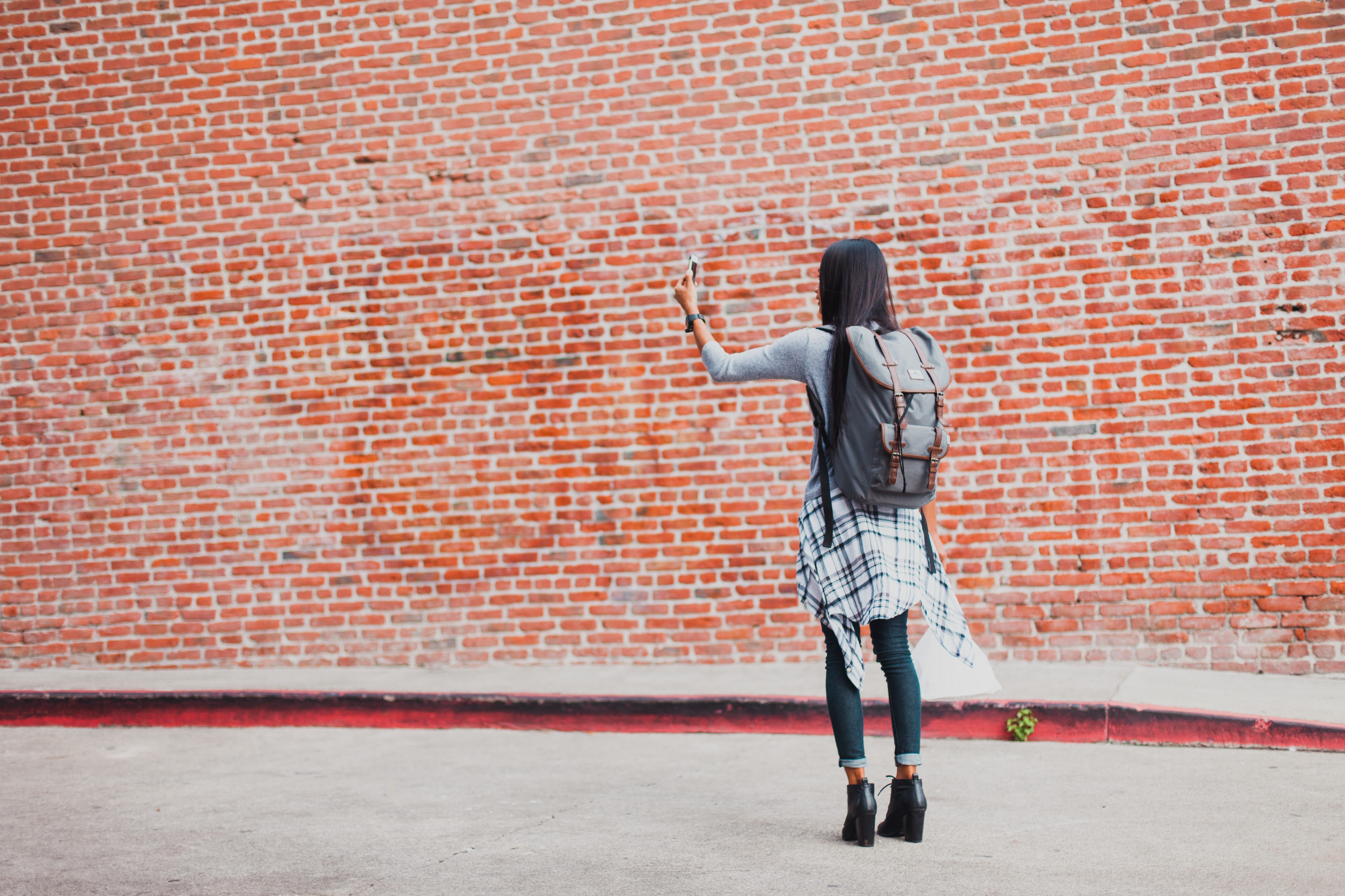 A young woman is taking a photo in front of a brick wall in Downtown.