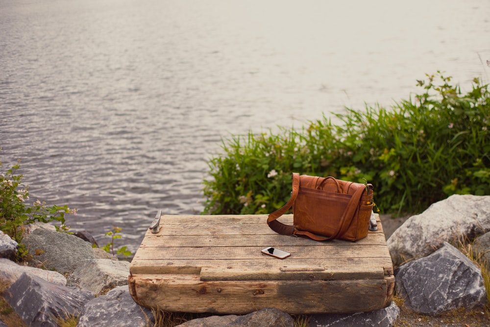 brown leather crossbody bag on brown wooden panel near water