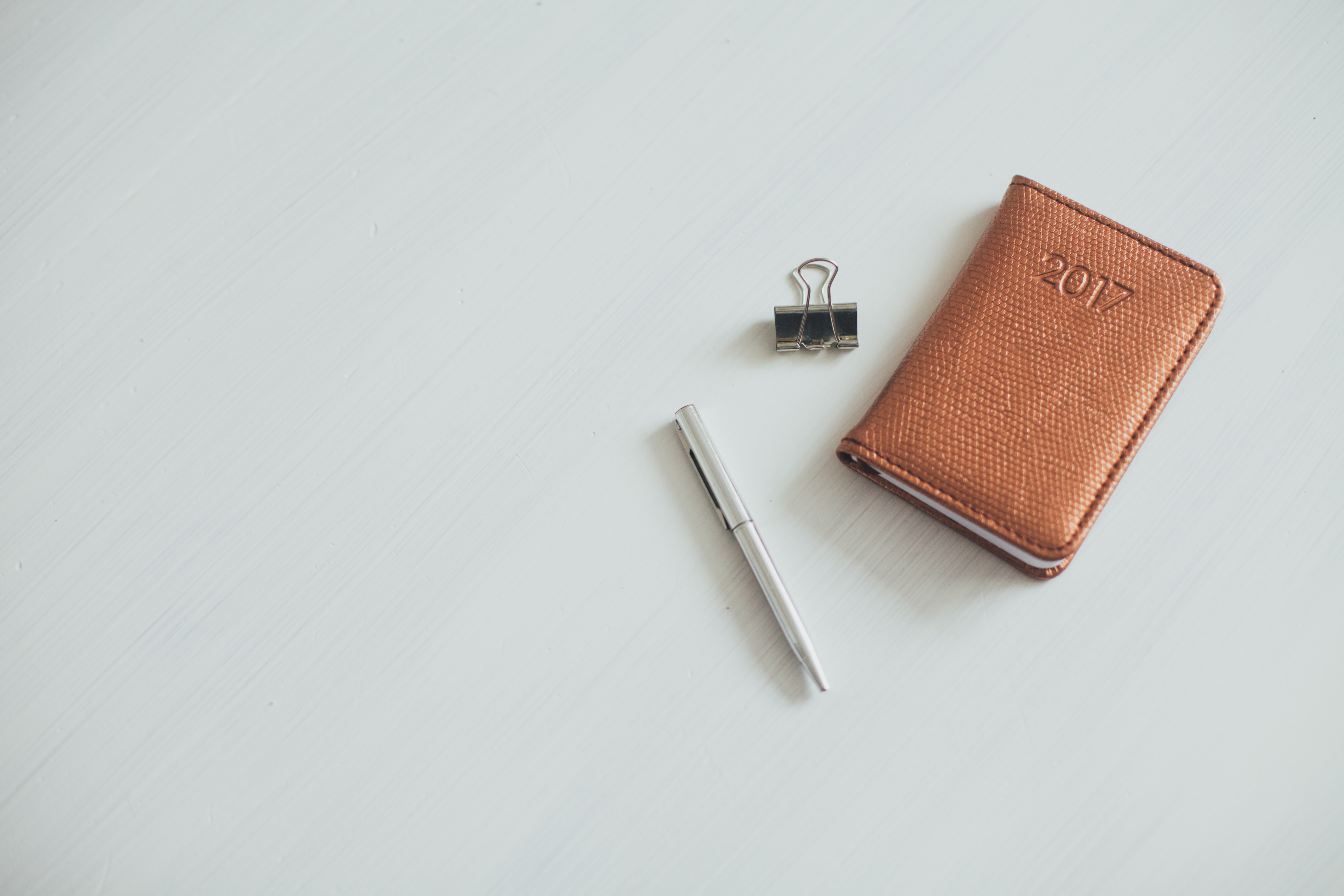A small notebook with a leather cover next to a pen and a bulldog clip