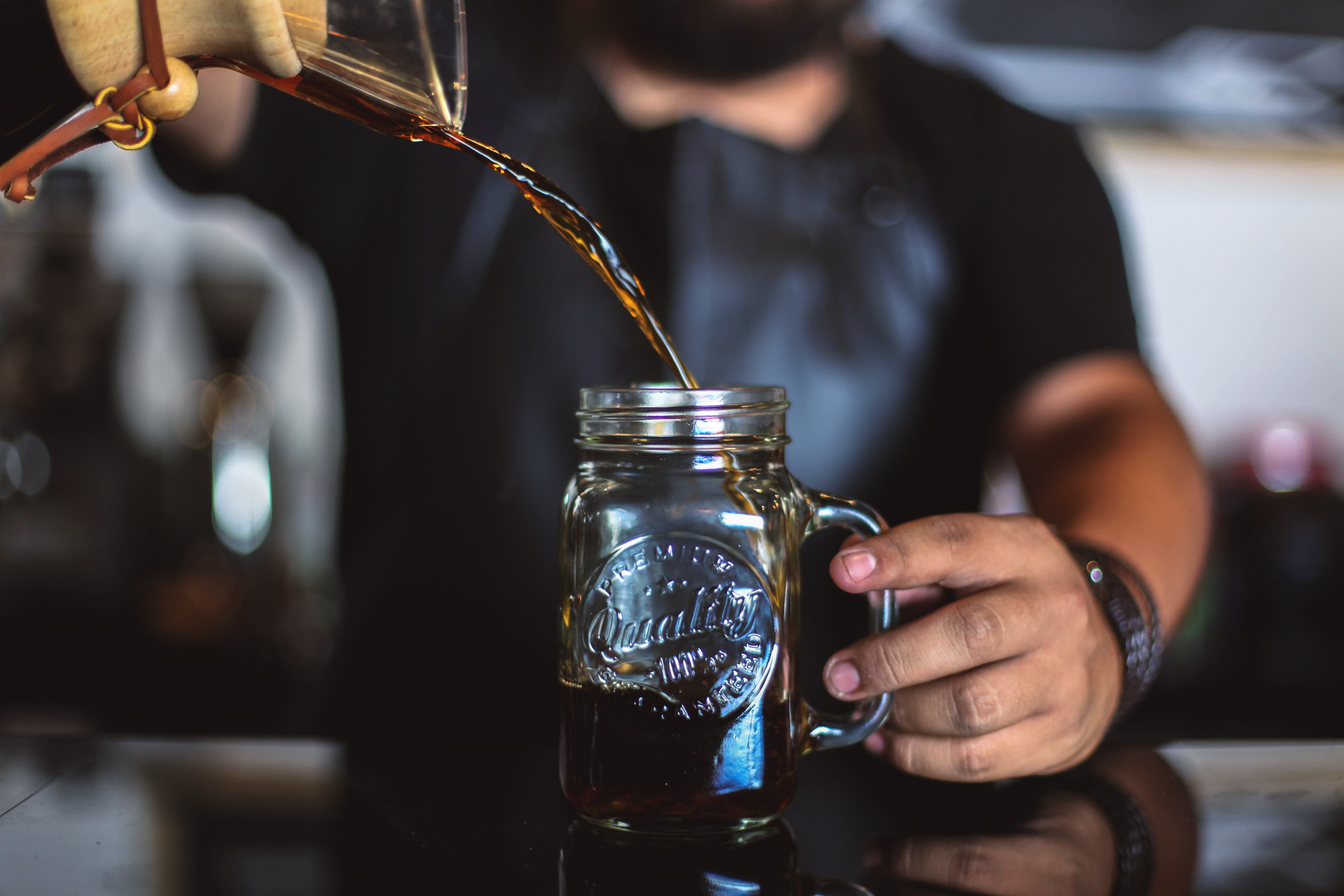 man pouring liquid on clear glass mason jar