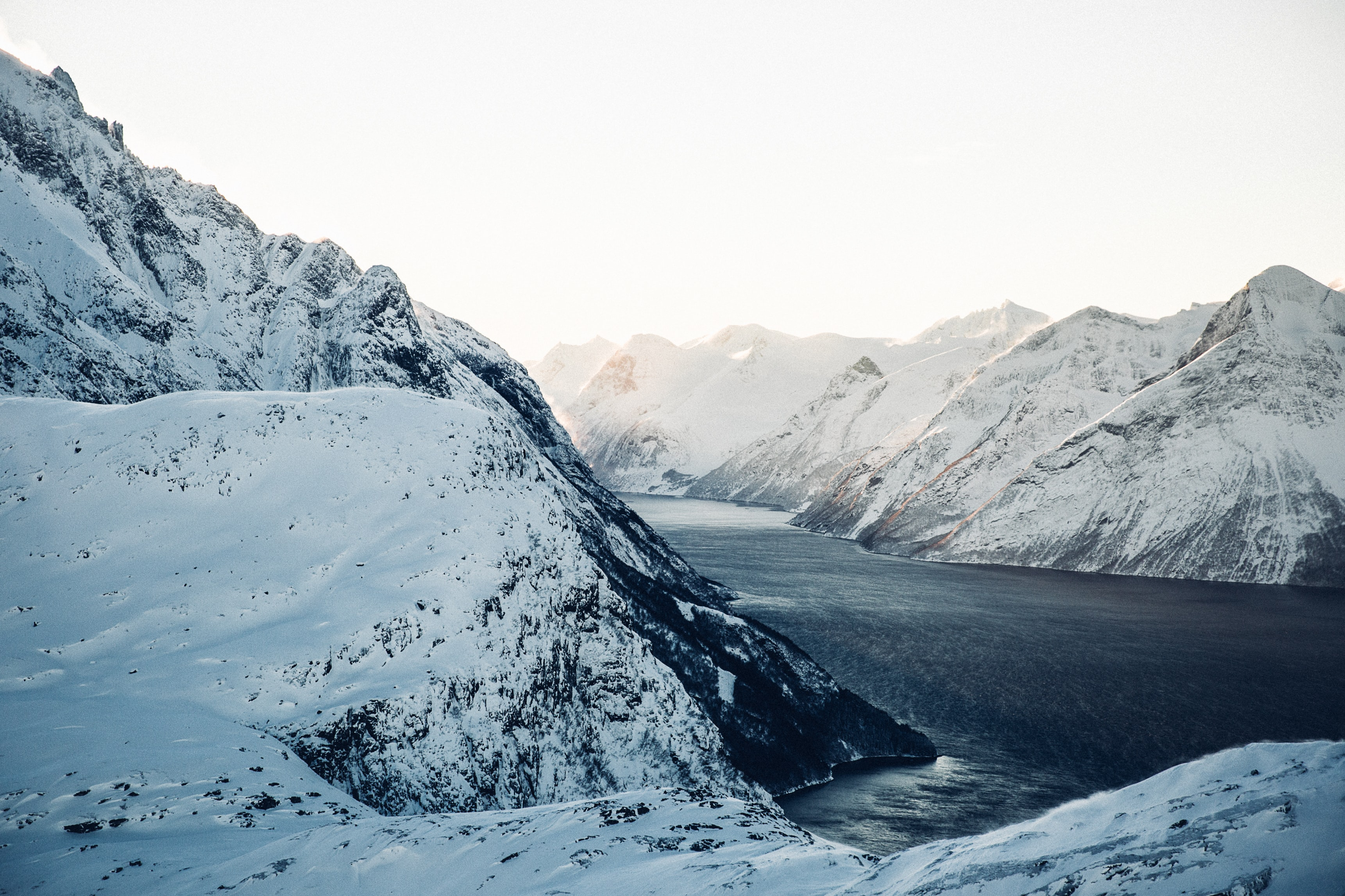landscape photography of snow-coated mountains near body of water during daytime