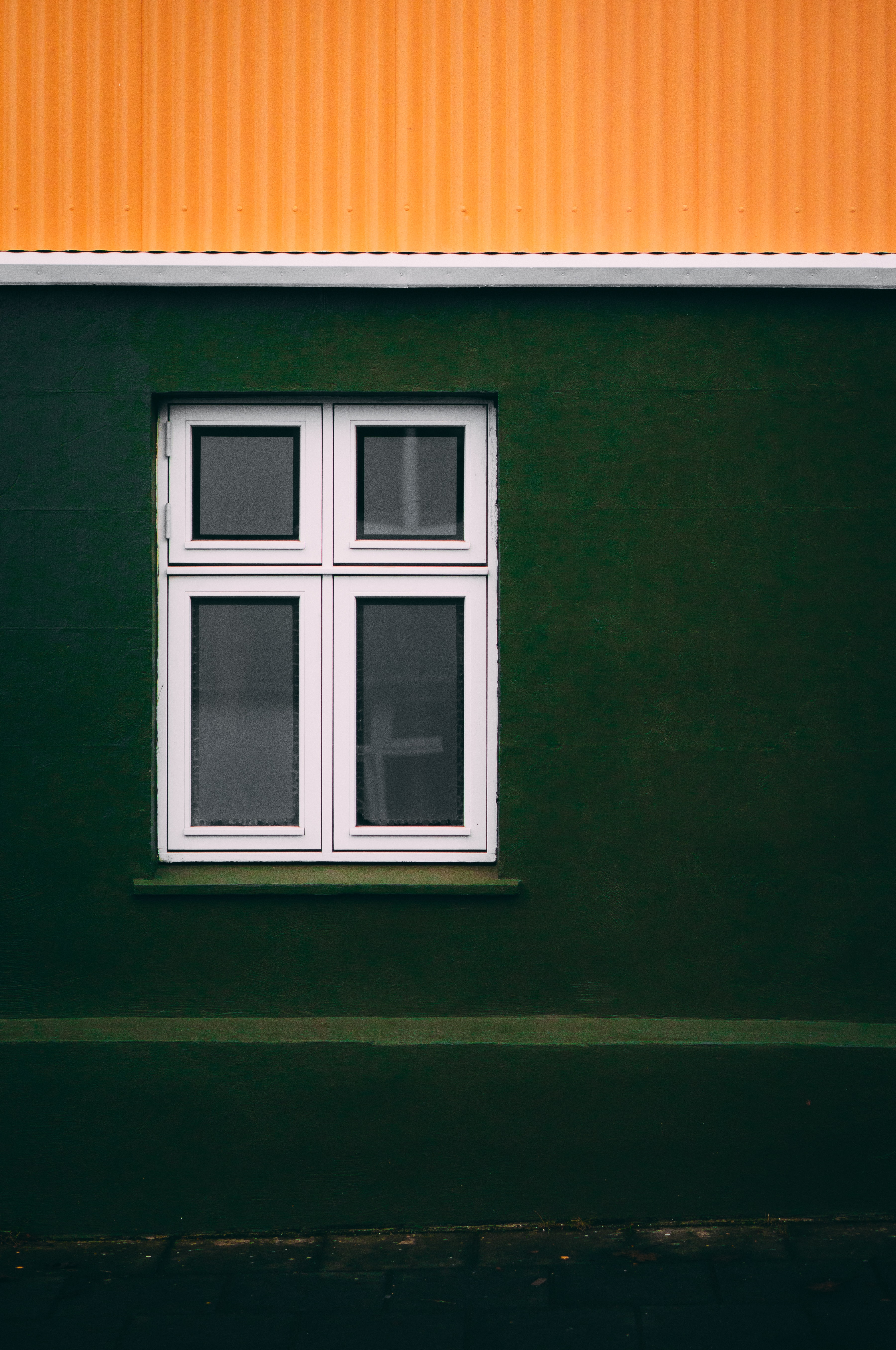 Window with white frame on green wall with orange roof in Reykjavík