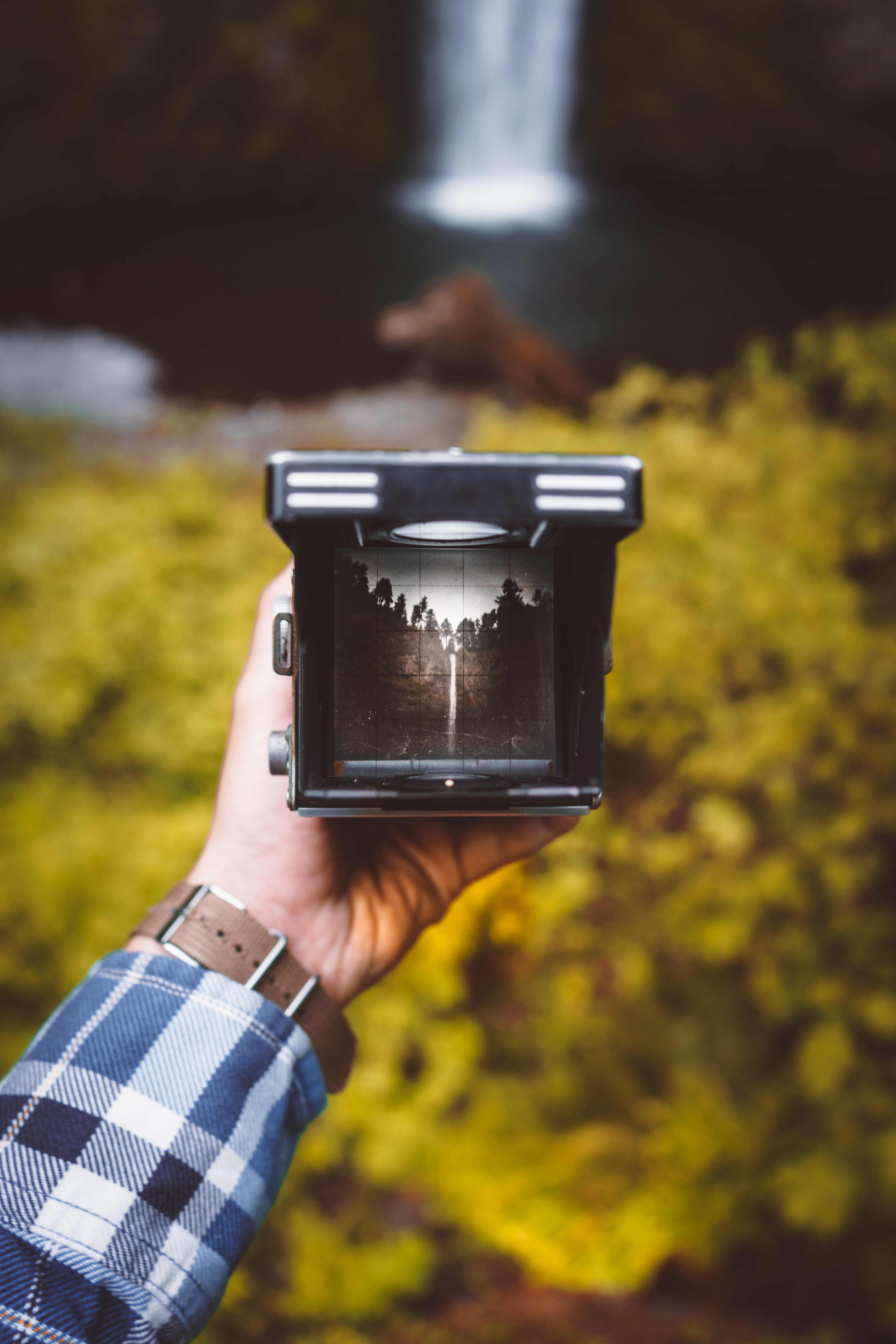 A person holding a viewfinder in their hand near a waterfall