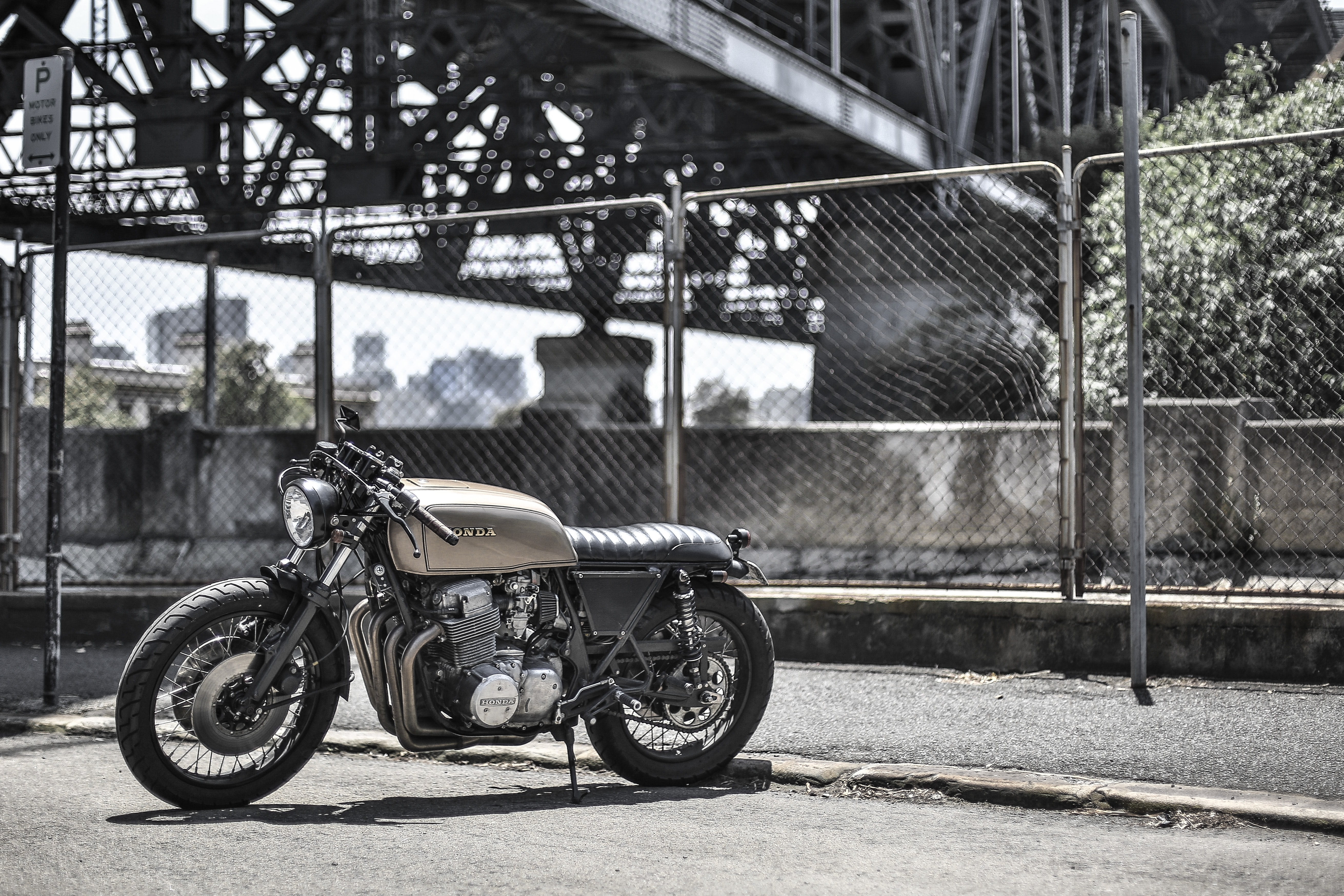 White and black motorcycle parked under an industrial bridge in front of a chain link fence