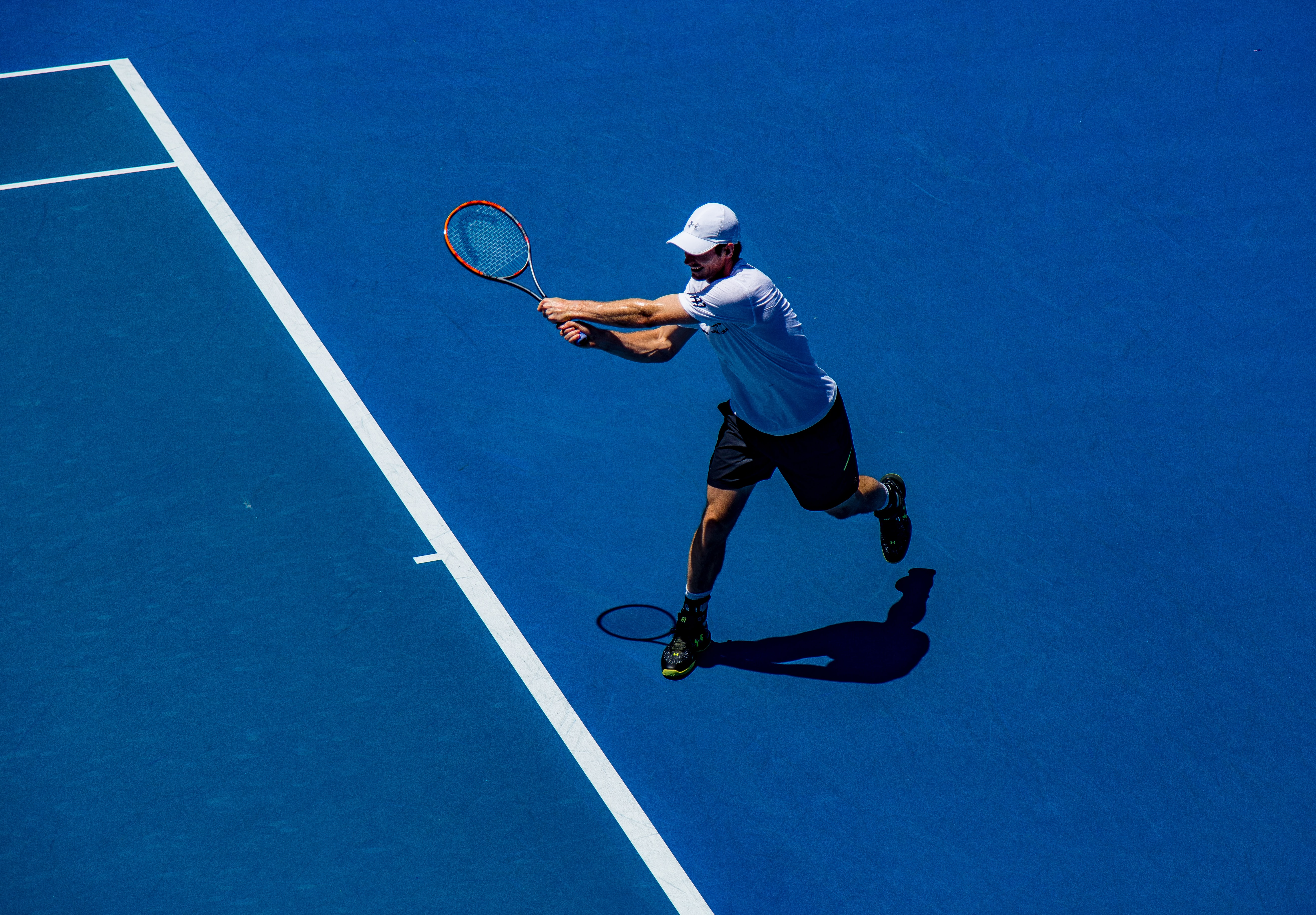 man playing tennis on field