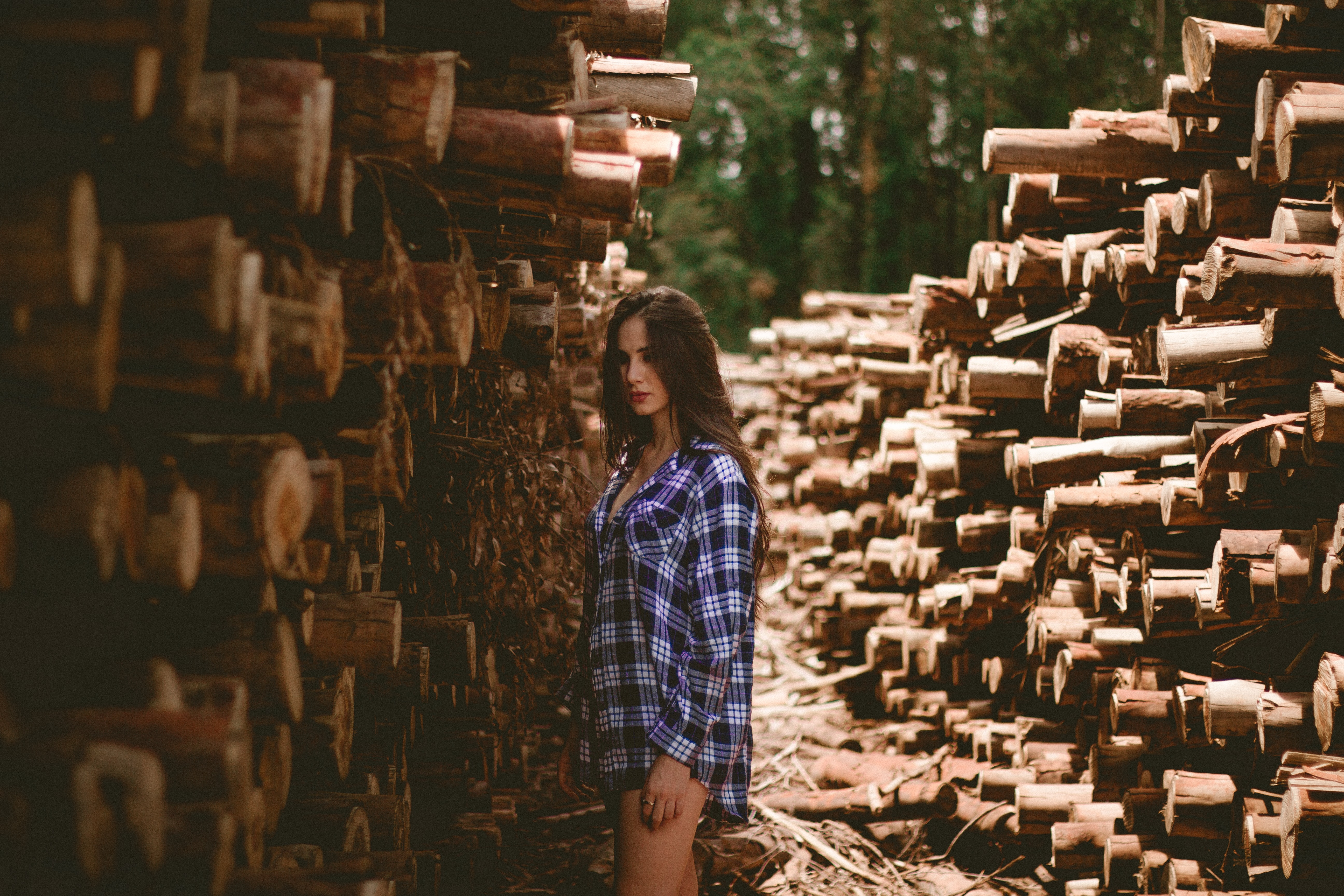 A woman in a plaid shirt stands aside stacks of lumber