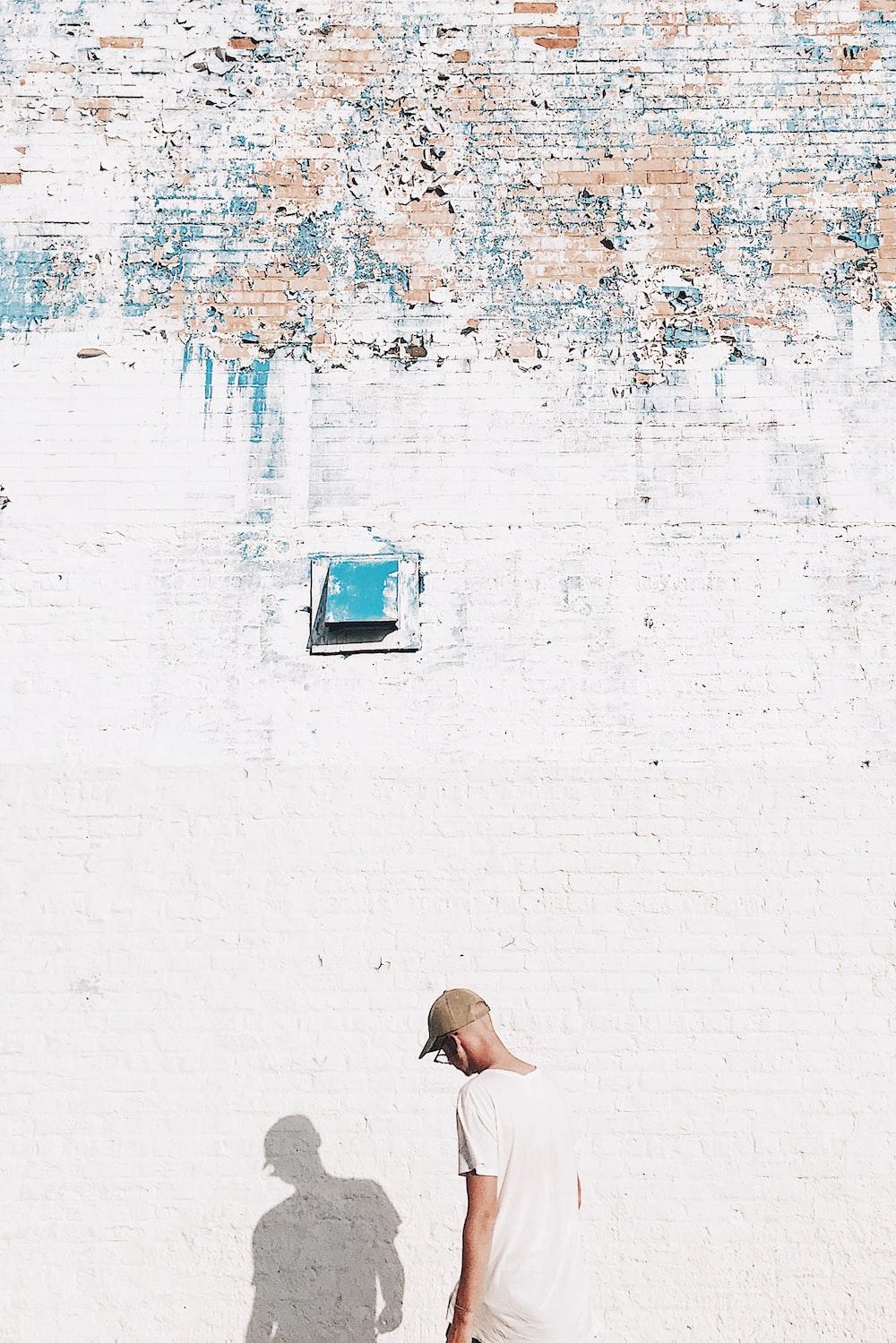 man standing facing white brick wall